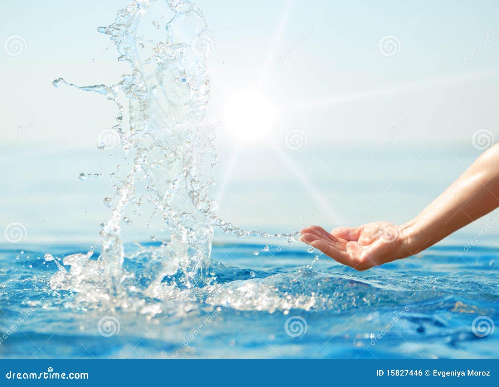 Mano que salpica el agua potable en rayos del sol