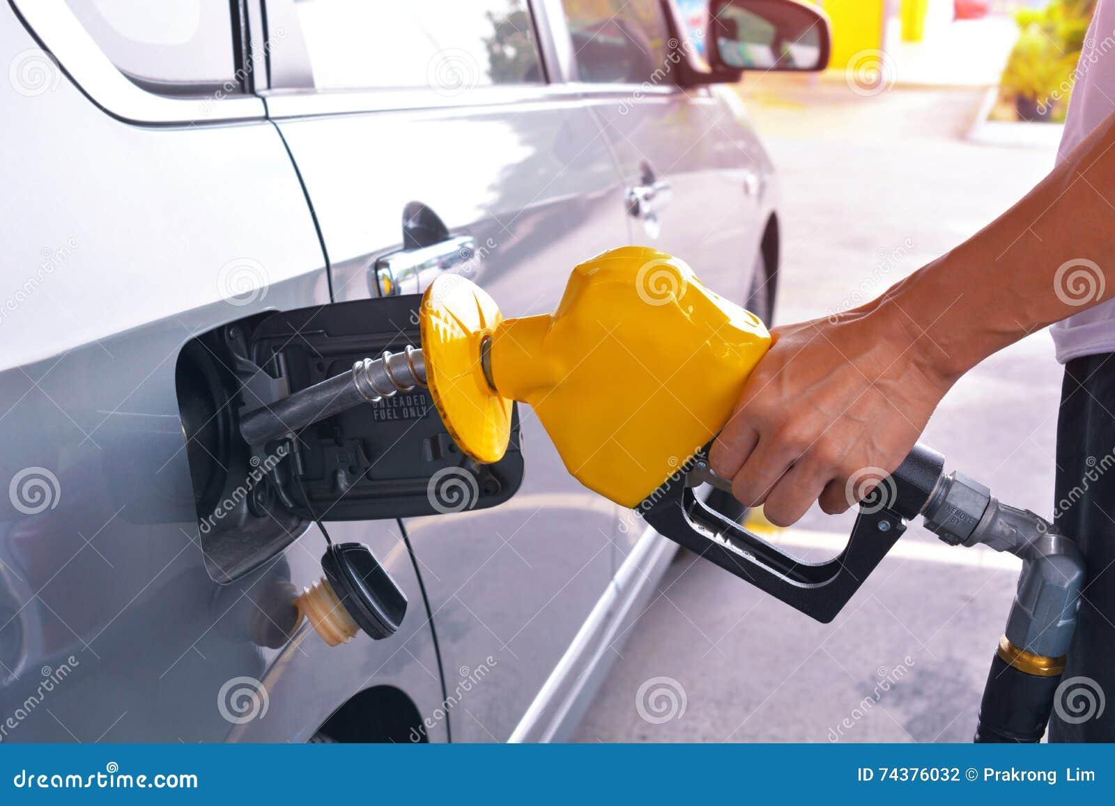Mano que sostiene el surtidor de gasolina para añadir el gas