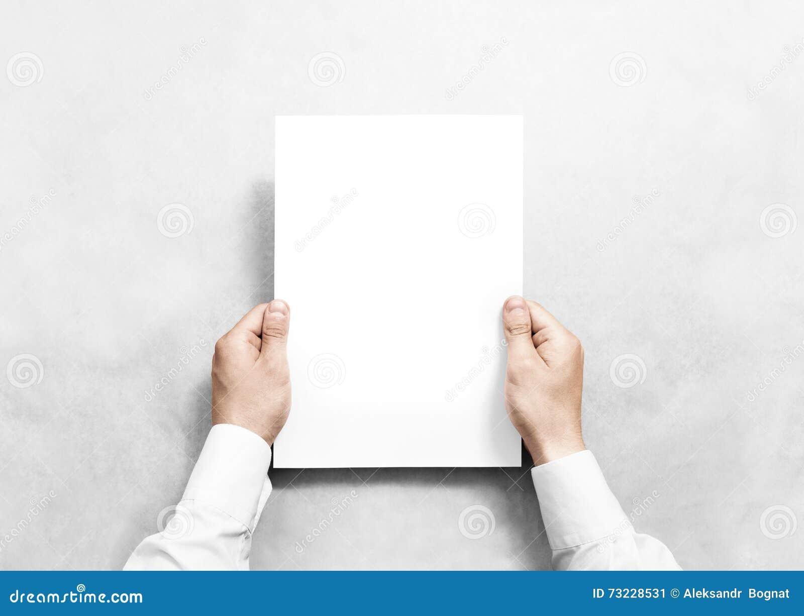 Mano que sostiene la maqueta blanca de la hoja del papel en blanco,