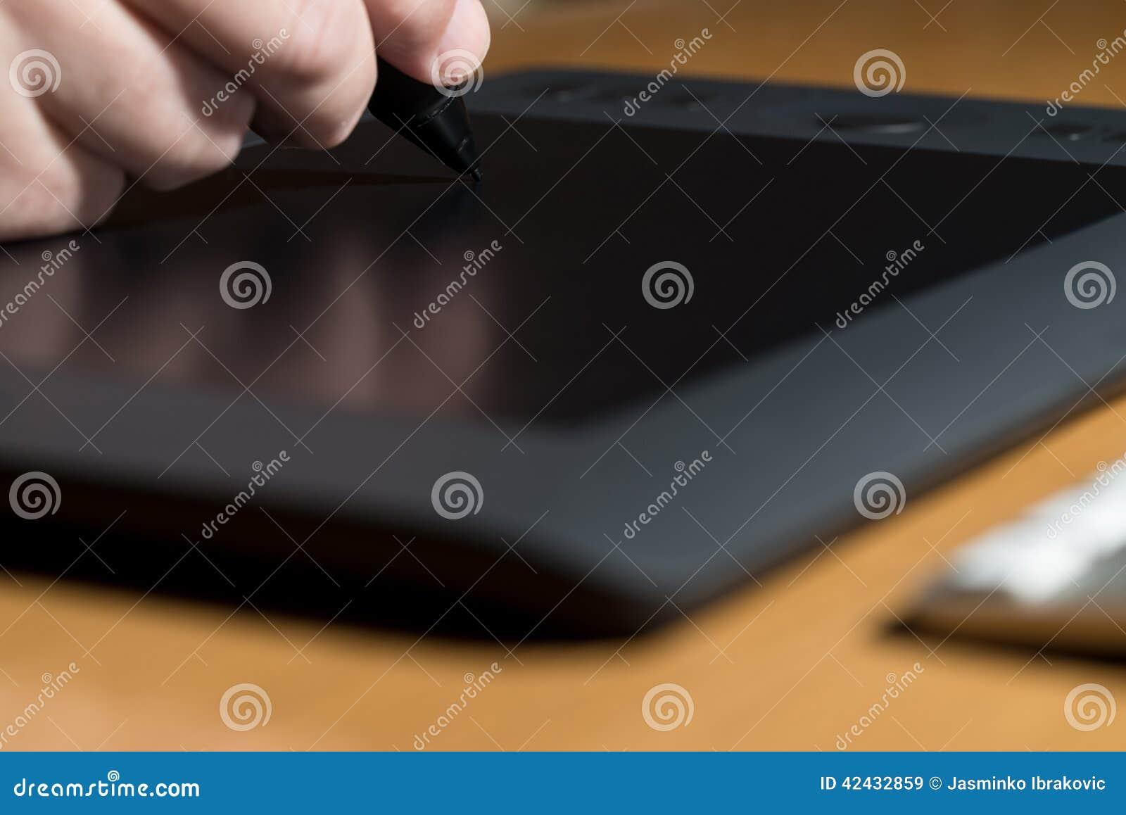 Mano que sostiene la tableta del dibujo para el diseñador gráfico