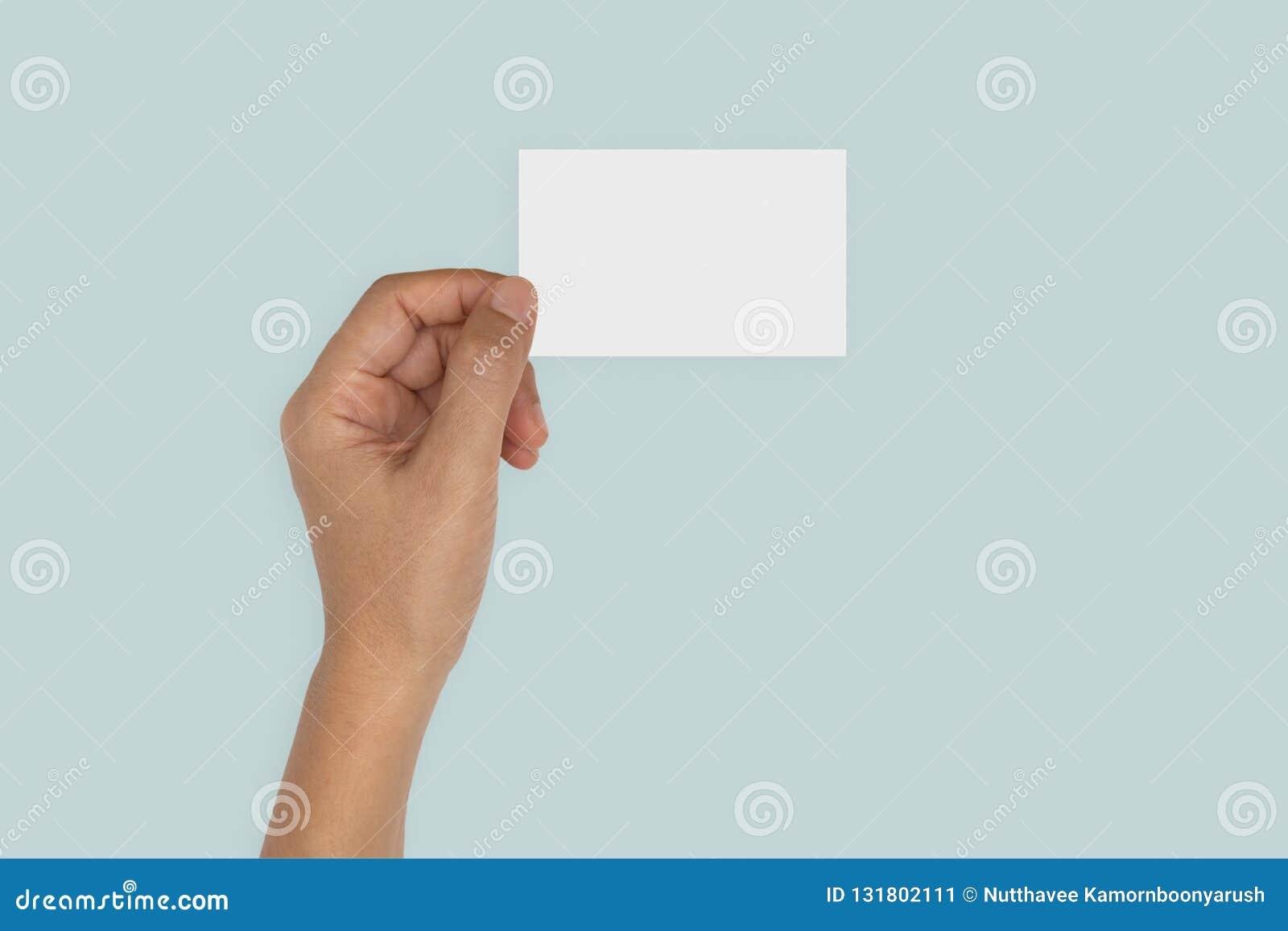 Mano que sostiene la tarjeta en blanco aislada en azul