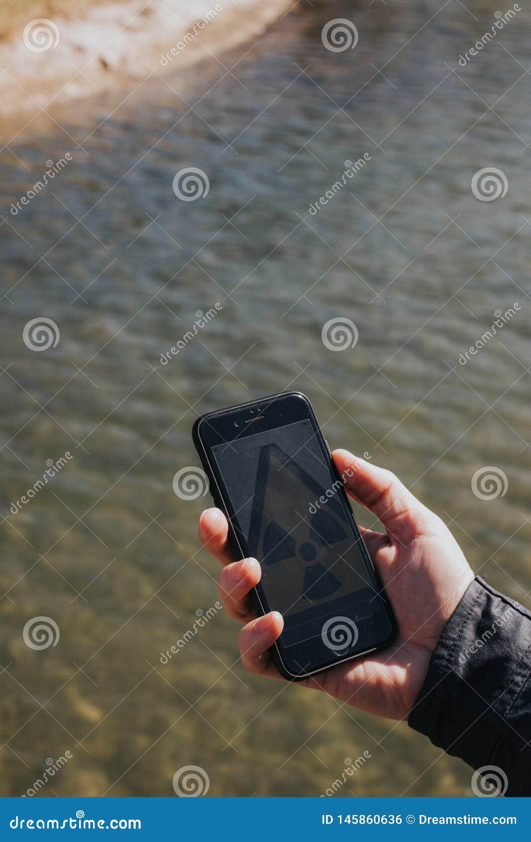 Mano que sostiene smartphone con el icono de la radiaci?n