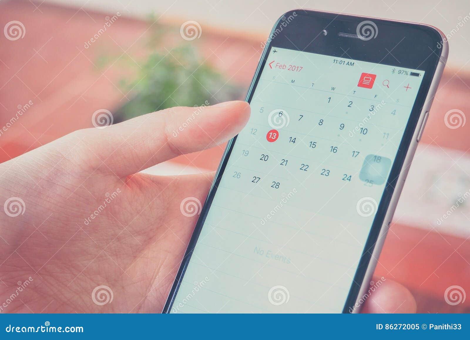 Mano que sostiene Smartphone mientras que mira el calendario