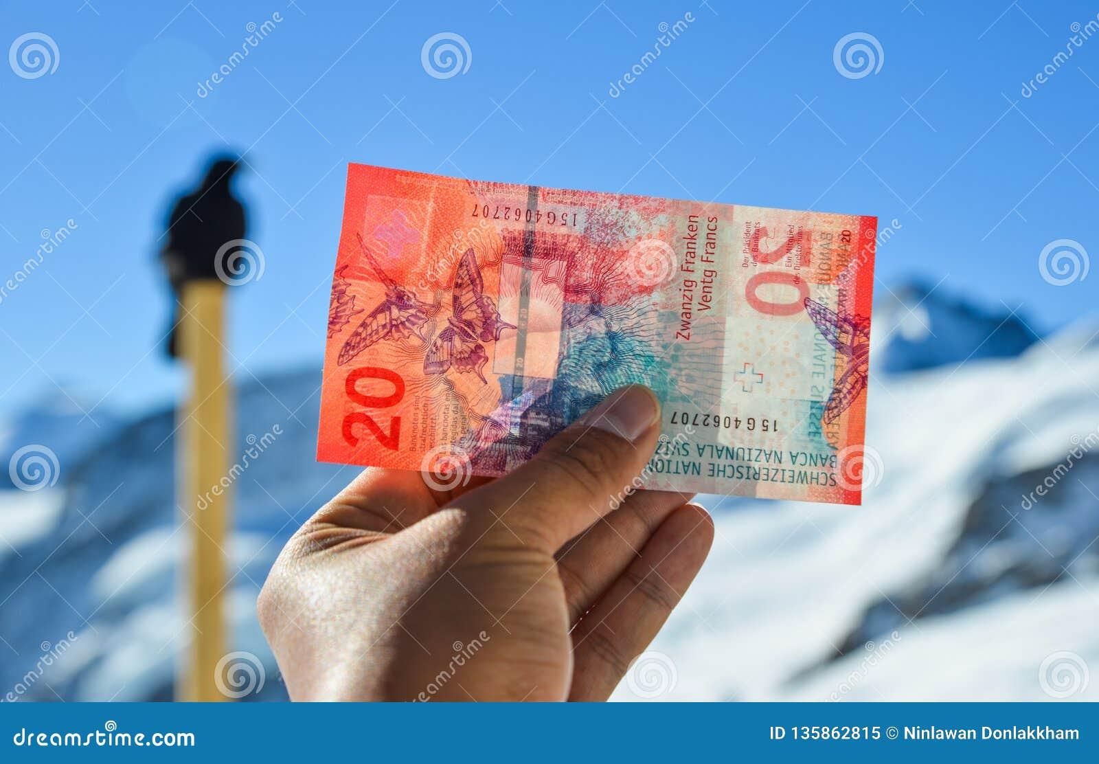 Mano que sostiene un billete de banco del franco suizo 20