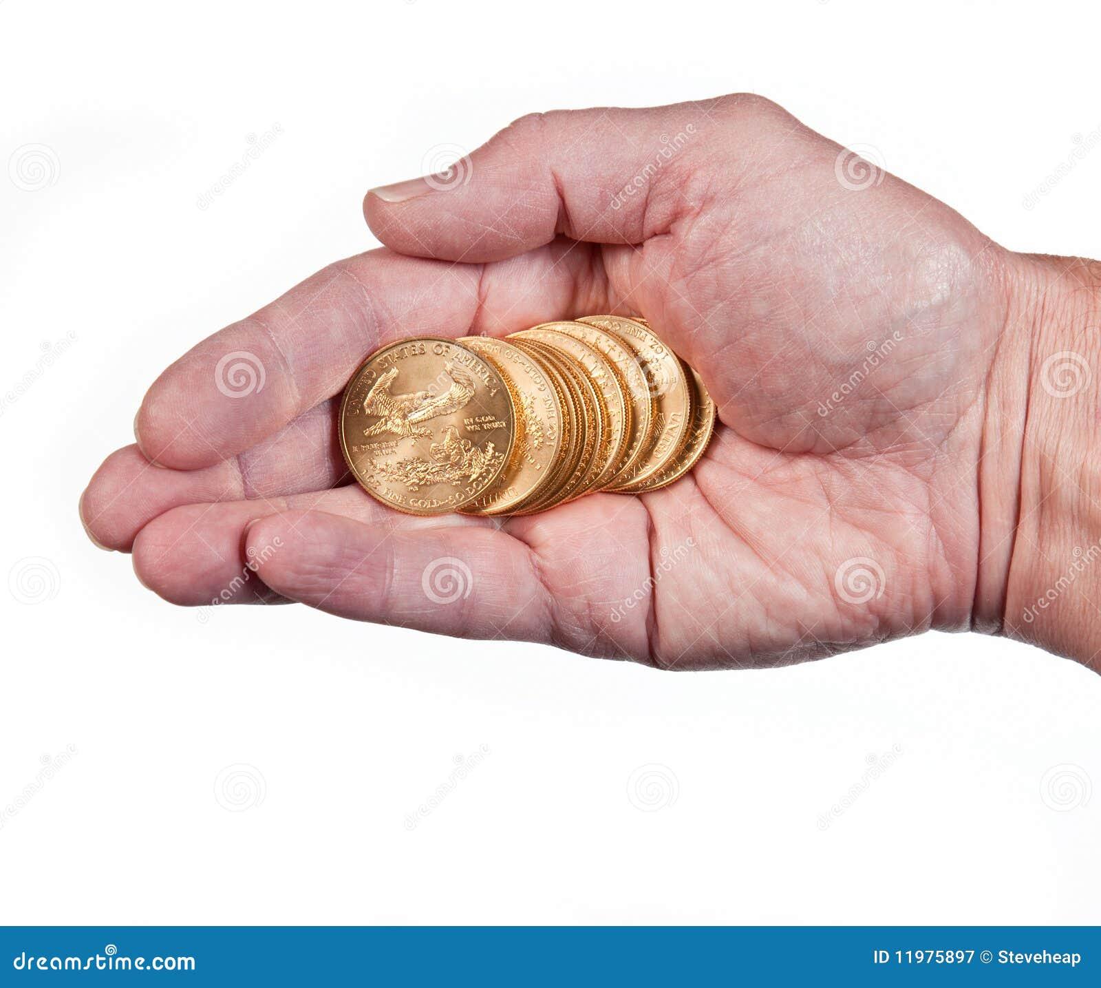Mano que sostiene una pila de monedas de oro