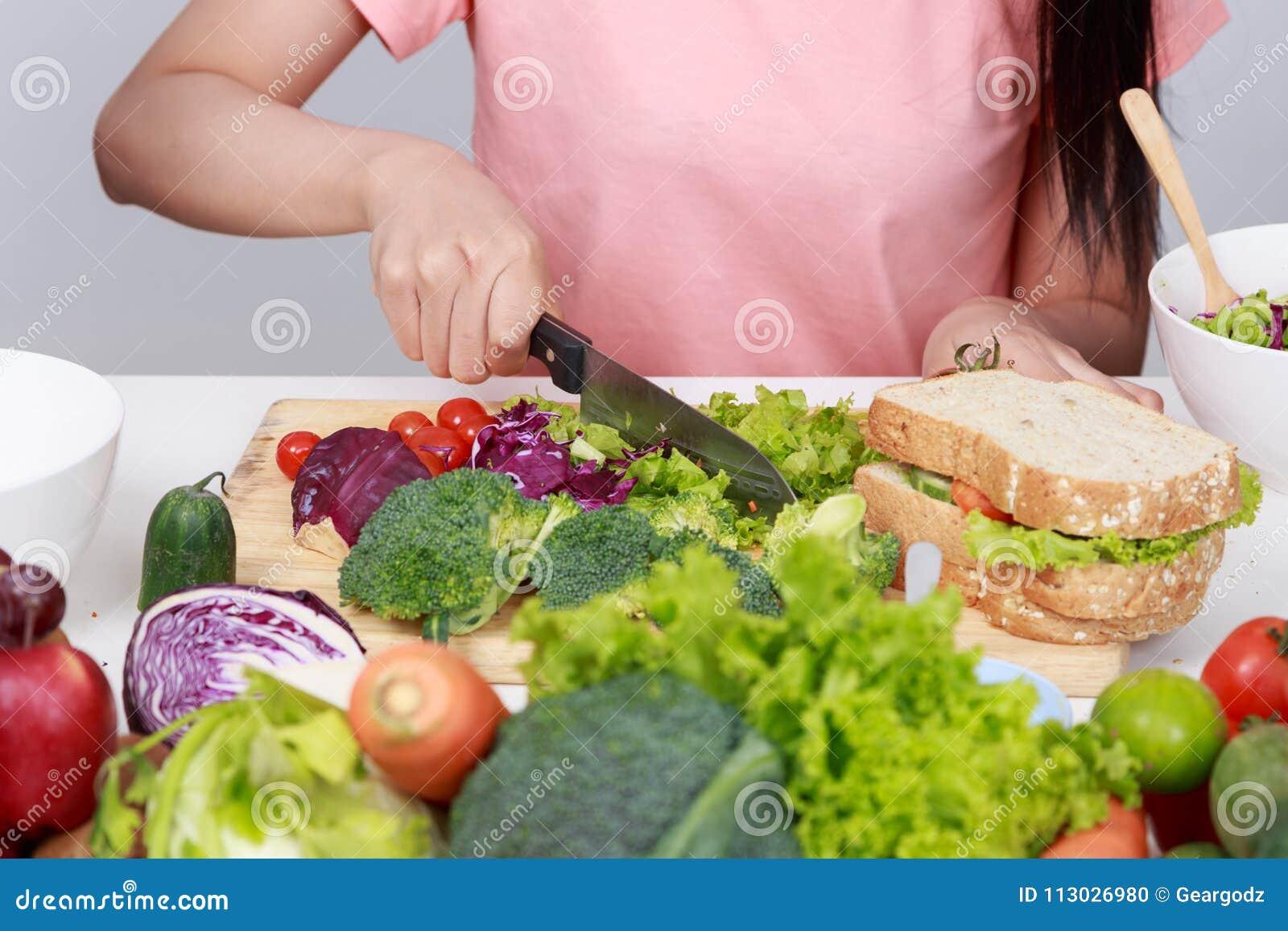 Mano usando el cuchillo a cortar el bróculi en sitio de la cocina