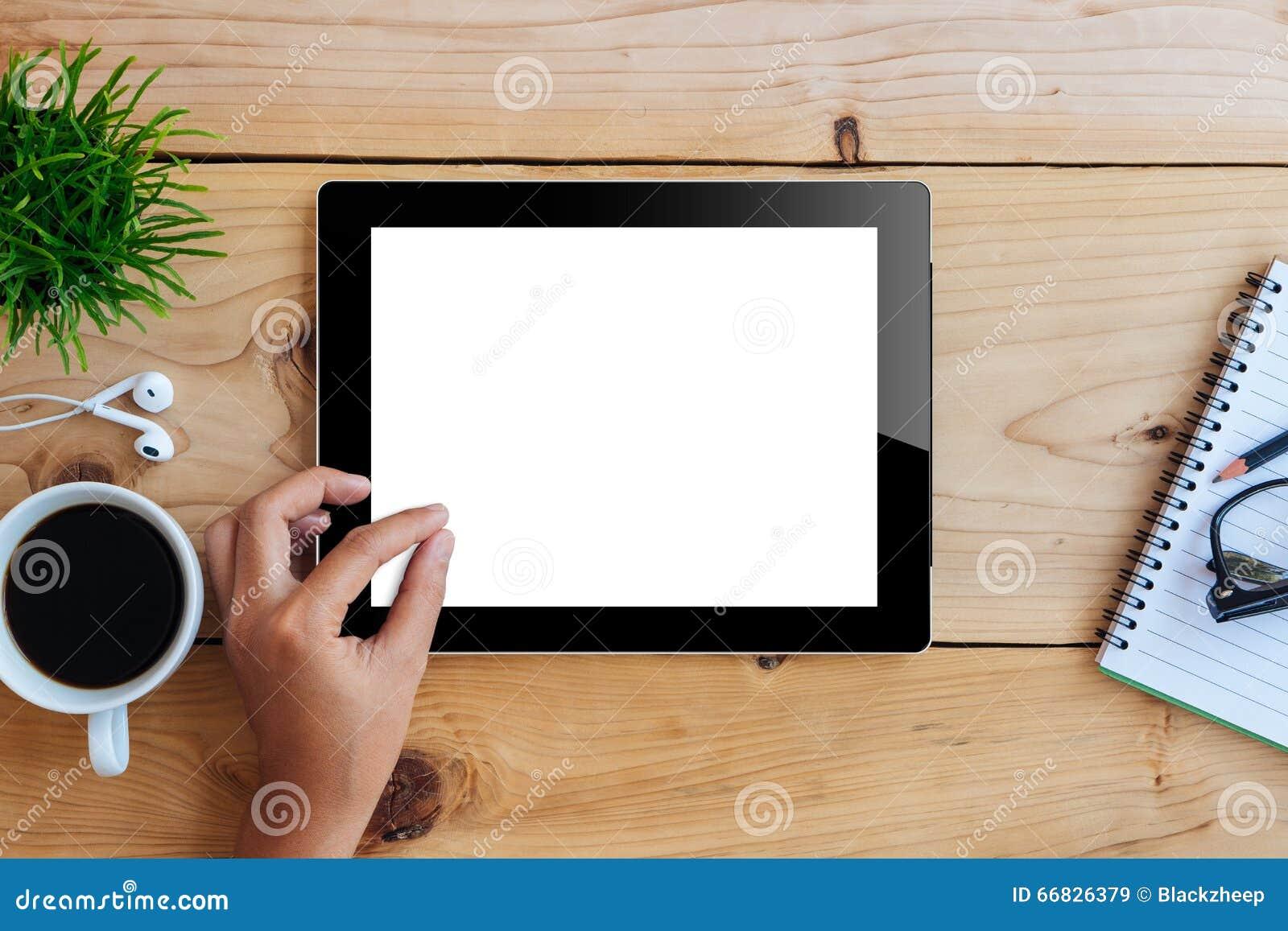 Mano usando la tableta de la maqueta en la exhibición blanca del escritorio de madera