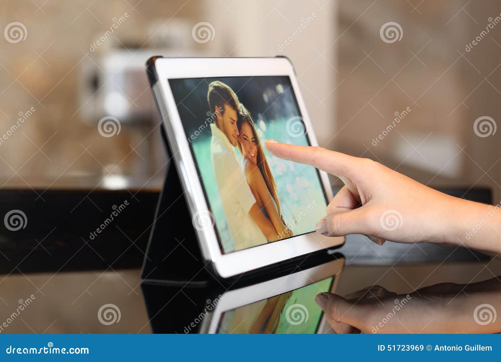 Mano usando las fotos de observación de una tableta en casa