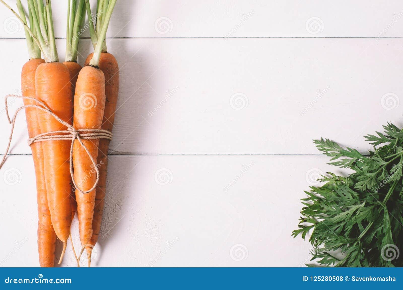 Manojo de zanahorias jovenes con los tops verdes en la tabla de madera blanca del vintage, comida sana en mofa encima de la opini