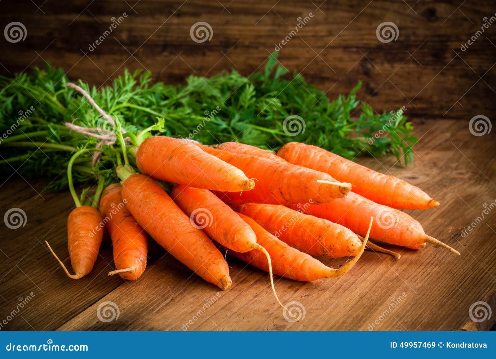 Manojo fresco de las zanahorias en la madera