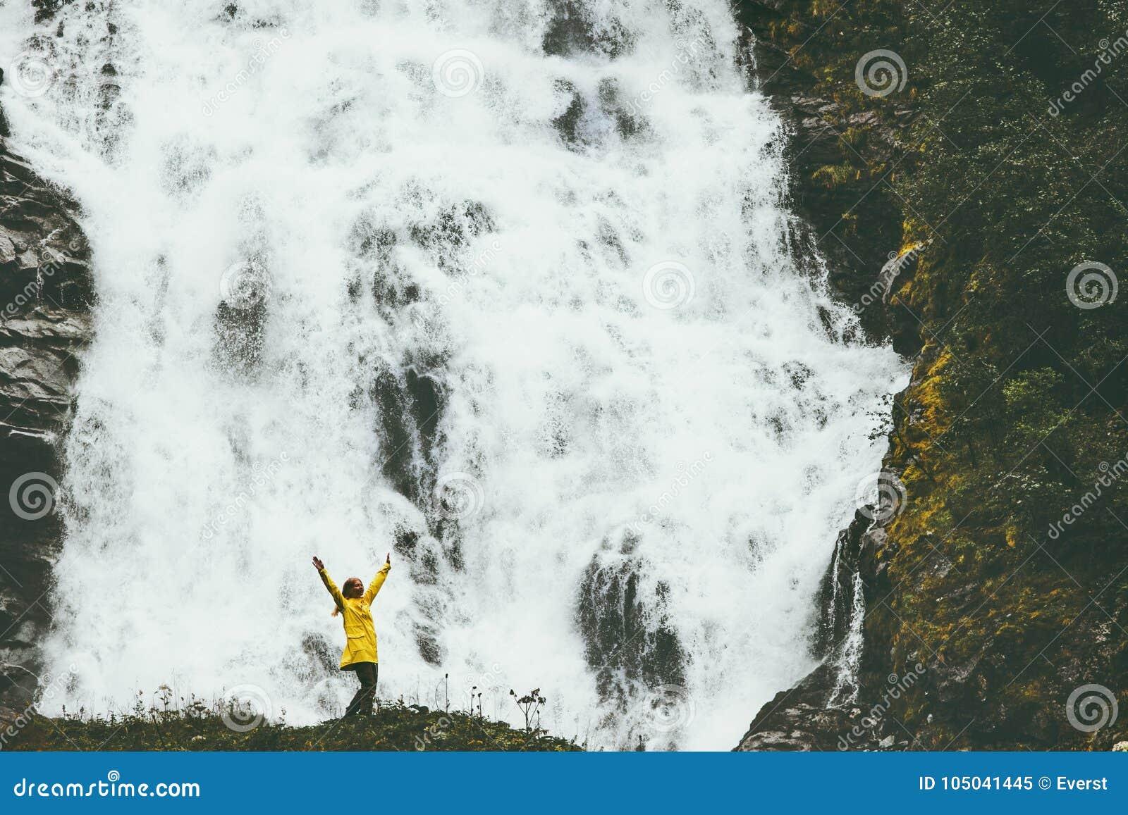 Manos aumentadas felices del aventurero de la mujer que gozan de la cascada grande