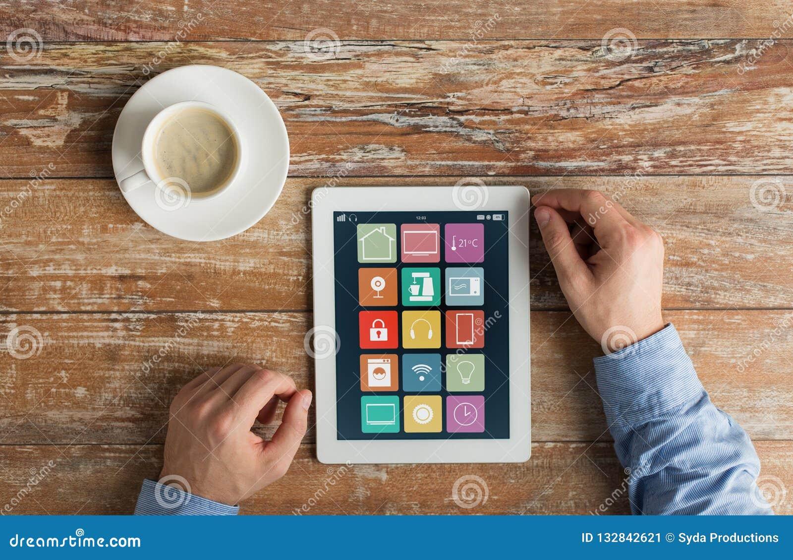 Manos con los iconos caseros elegantes en la tableta