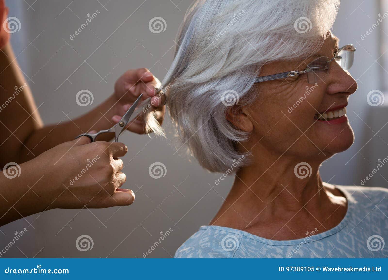 Manos cosechadas del pelo del corte del hairsylist de la mujer mayor