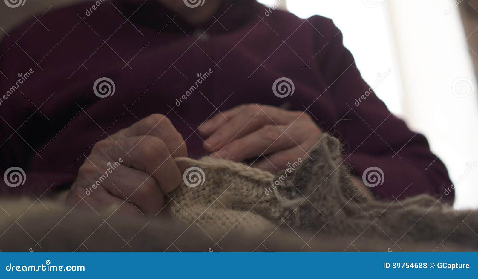 Manos de la abuela del primer que hacen punto el suéter
