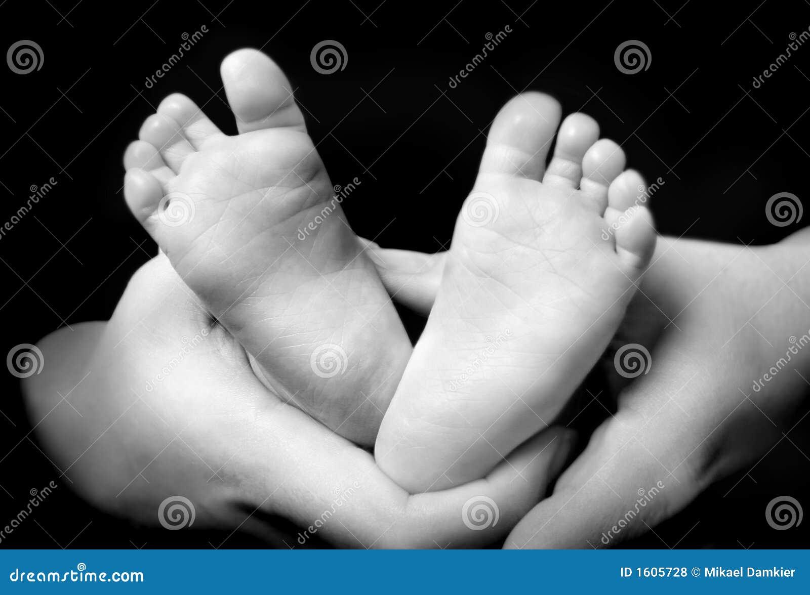 Manos de la madre holdning el suyo pies del hijo