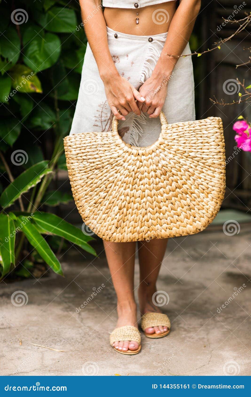 Manos de la mujer con el bolso de la paja