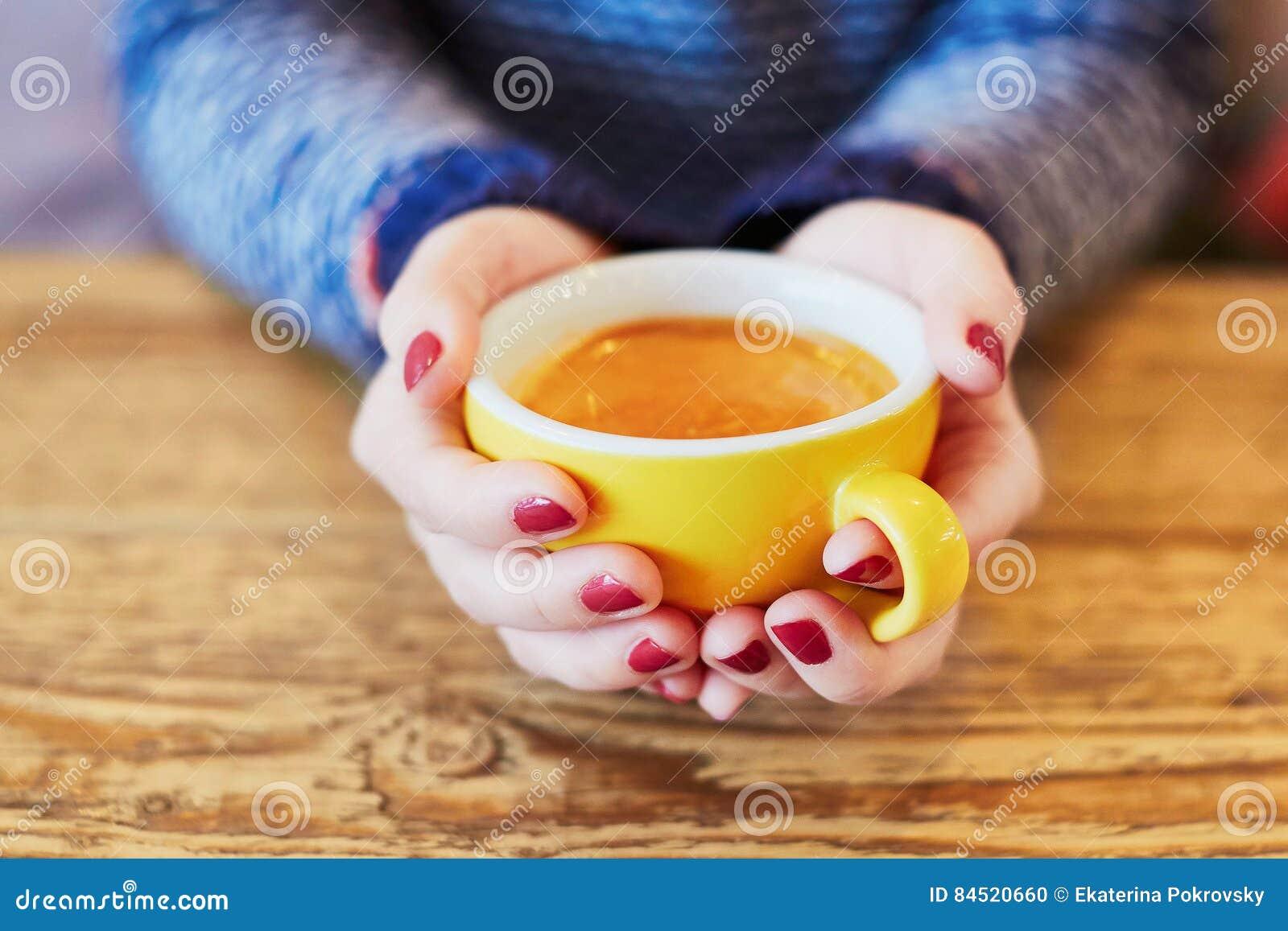 Manos de la mujer con la manicura y la taza rojas de café caliente fresco en la tabla de madera