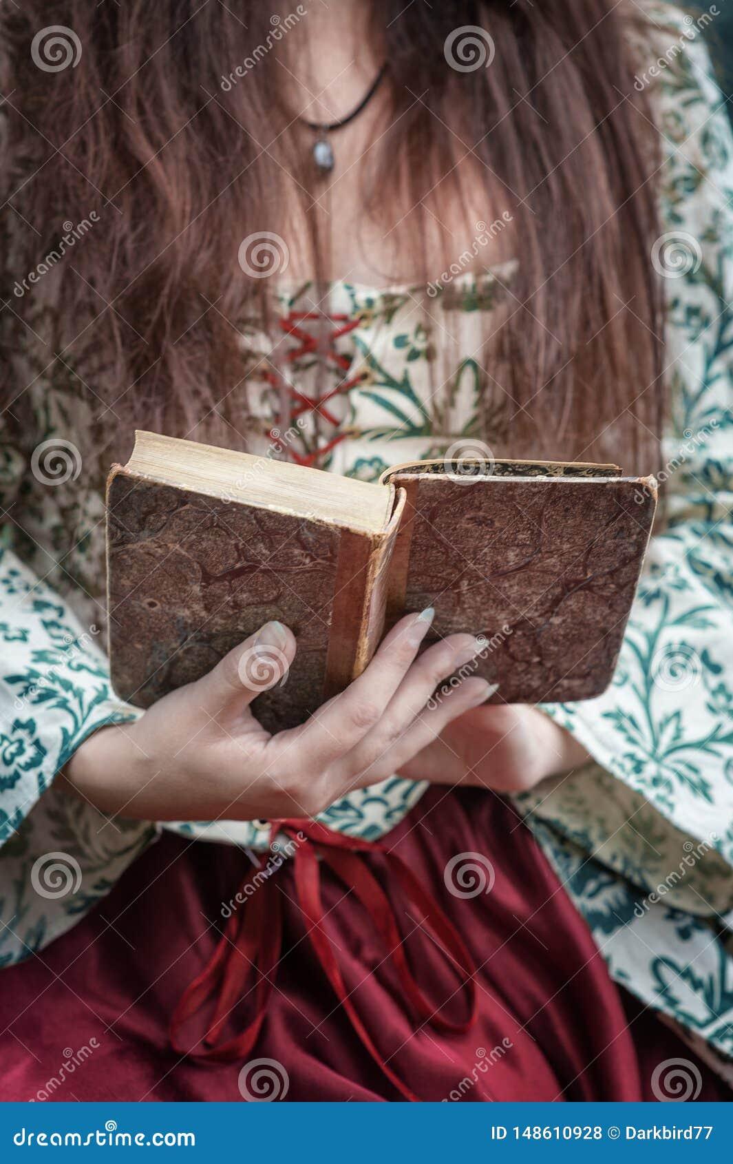 Manos de la mujer en el vestido medieval que sostiene el libro viejo del vintage