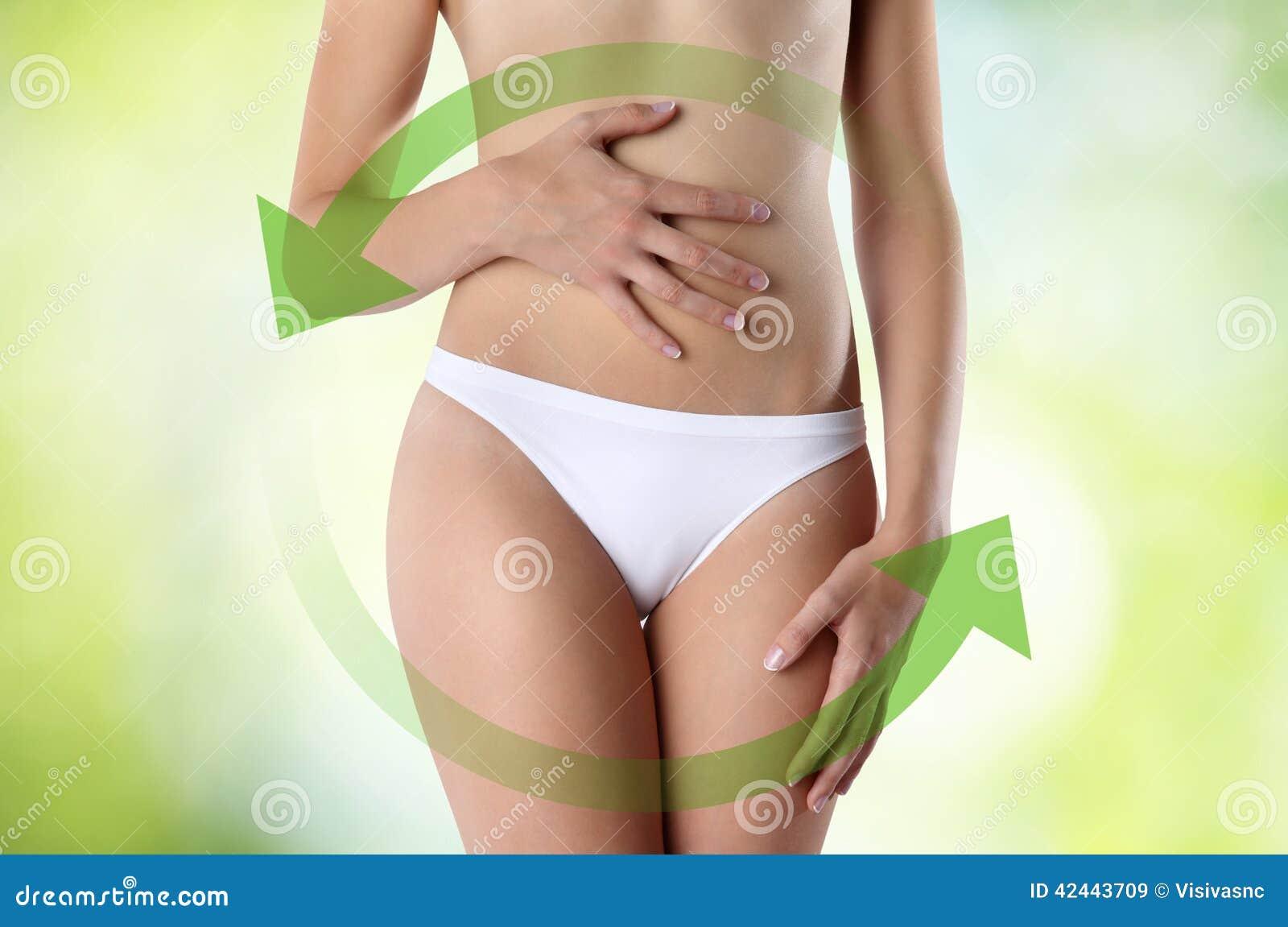 Manos de la mujer en el vientre con la flecha verde