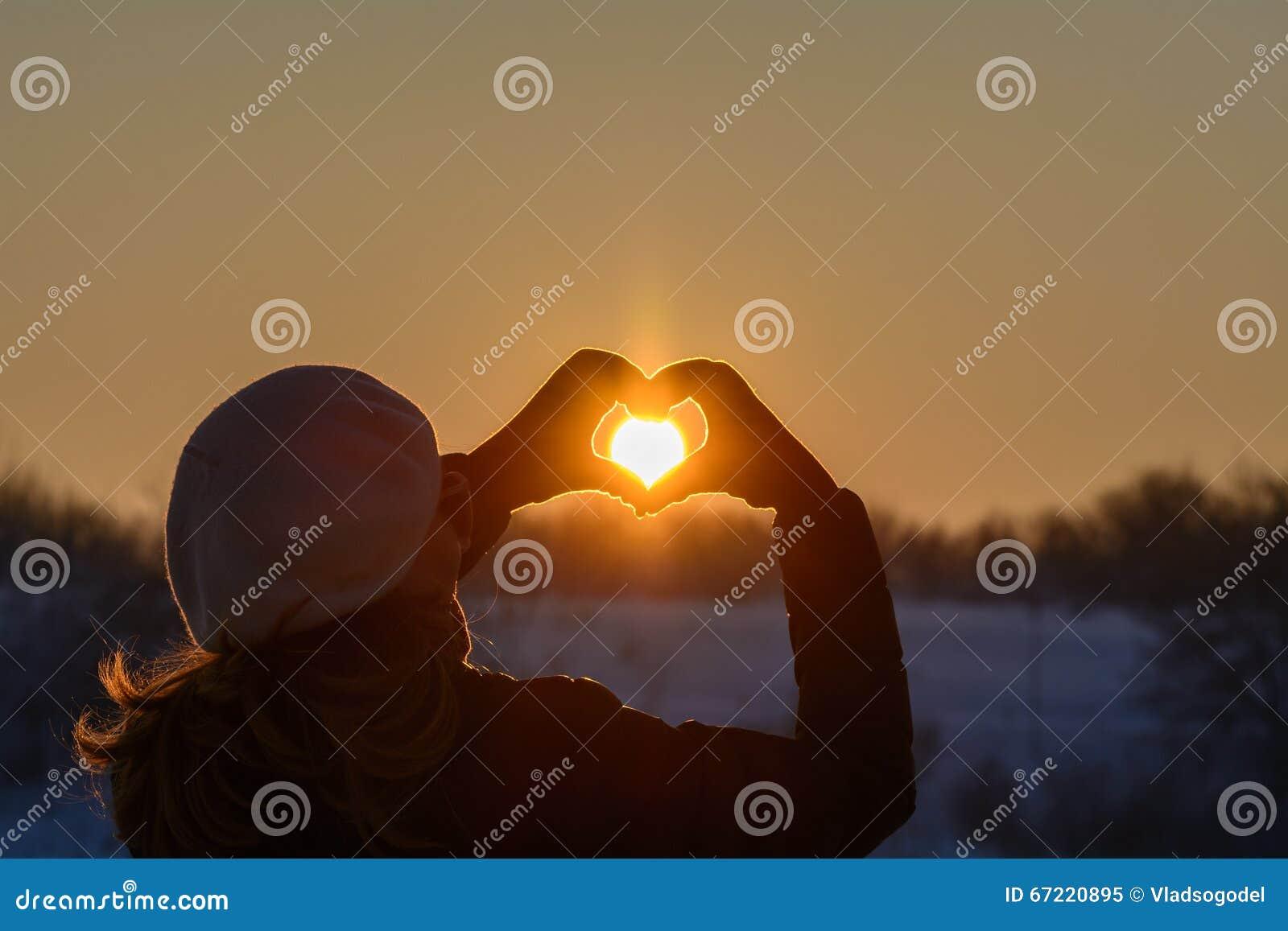 Manos de la mujer en guantes del invierno Símbolo del corazón formado, forma de vida y