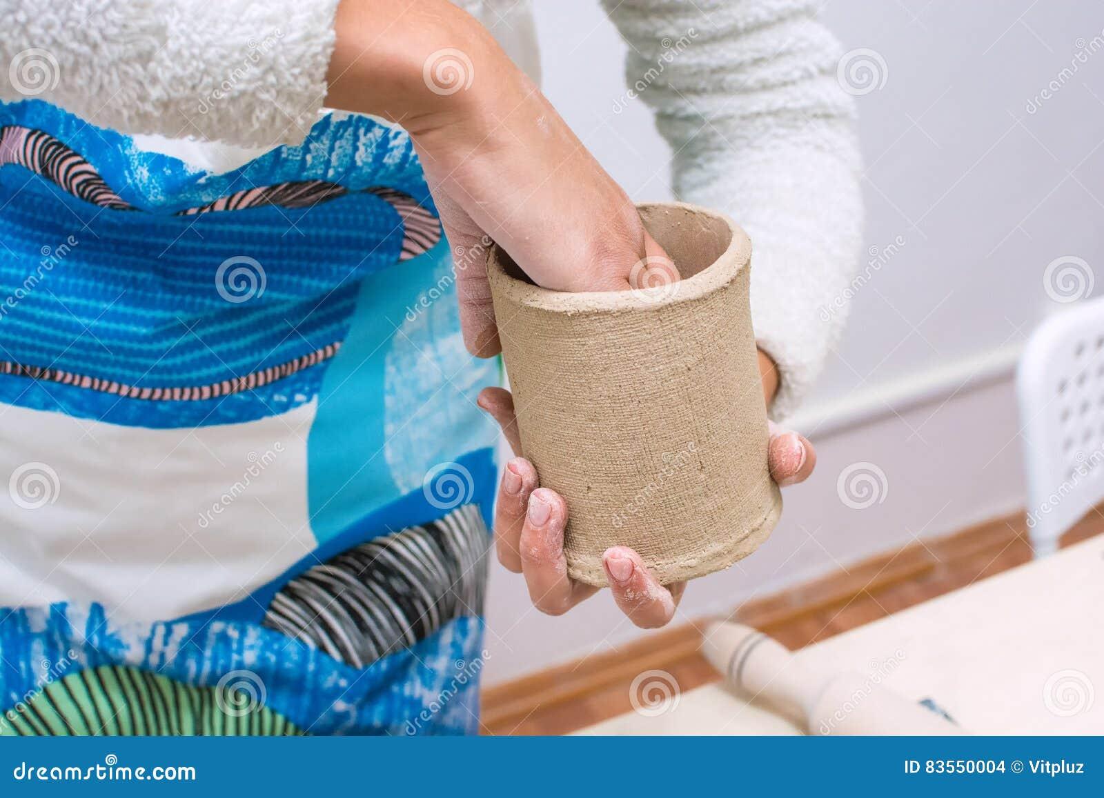 Manos de la mujer joven que hacen una taza de la arcilla cruda