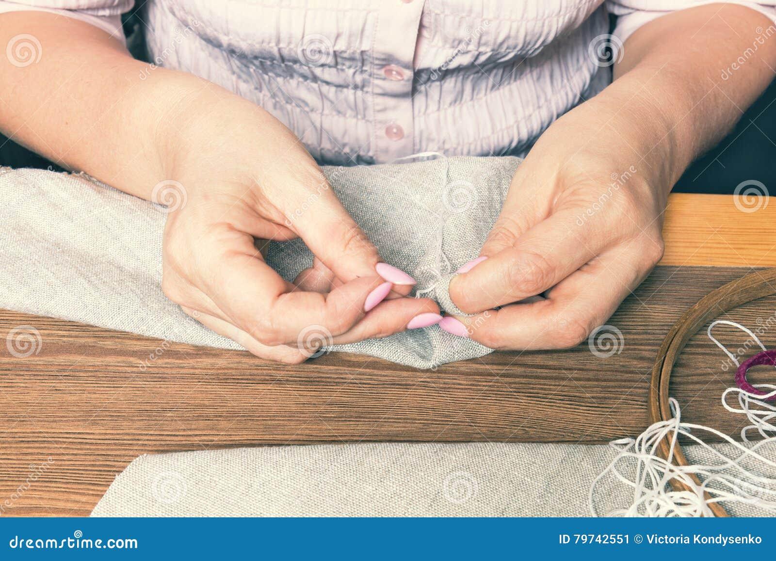 Manos de la mujer que hacen el bordado a cielo abierto
