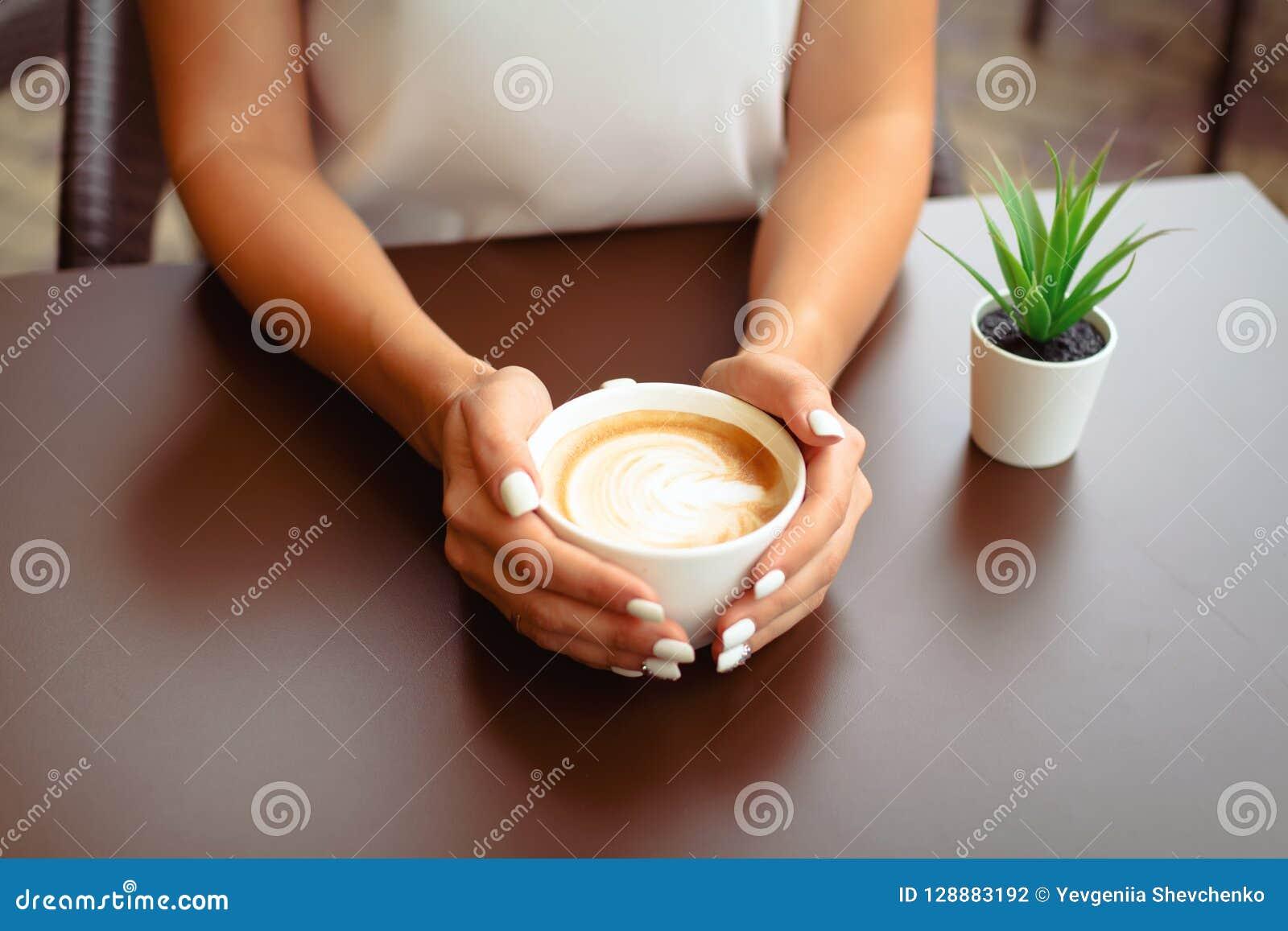 Manos de la mujer que llevan a cabo arte del cappucino o del latte
