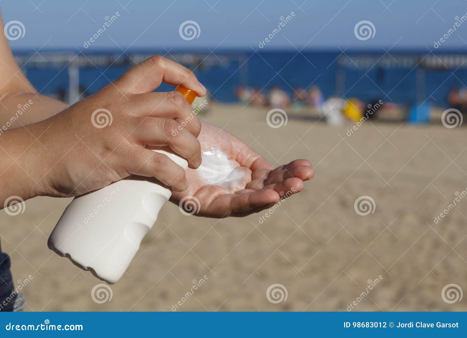 Manos de la mujer que ponen la protección solar en la playa