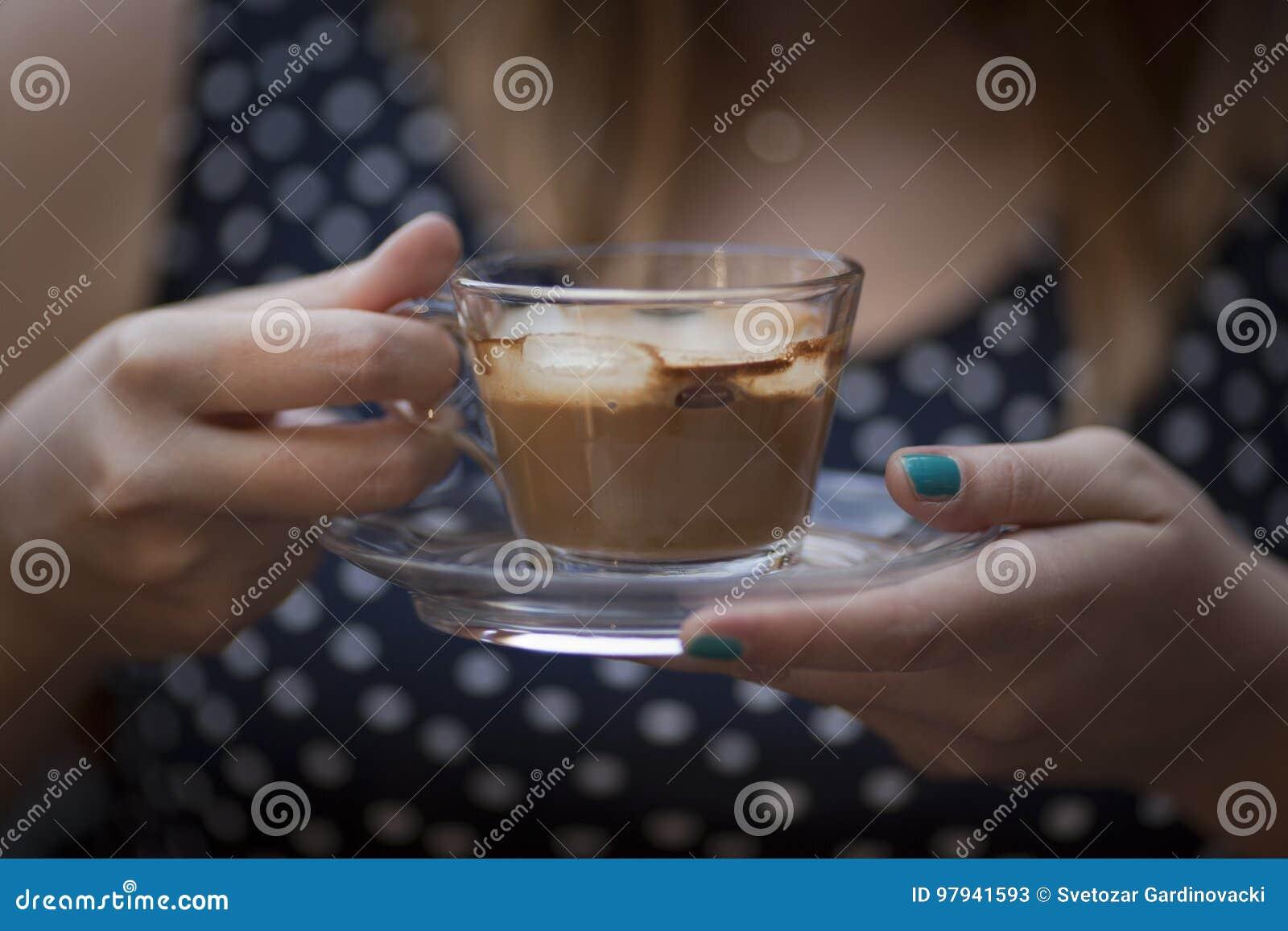 Manos de la mujer que sostienen la taza de café