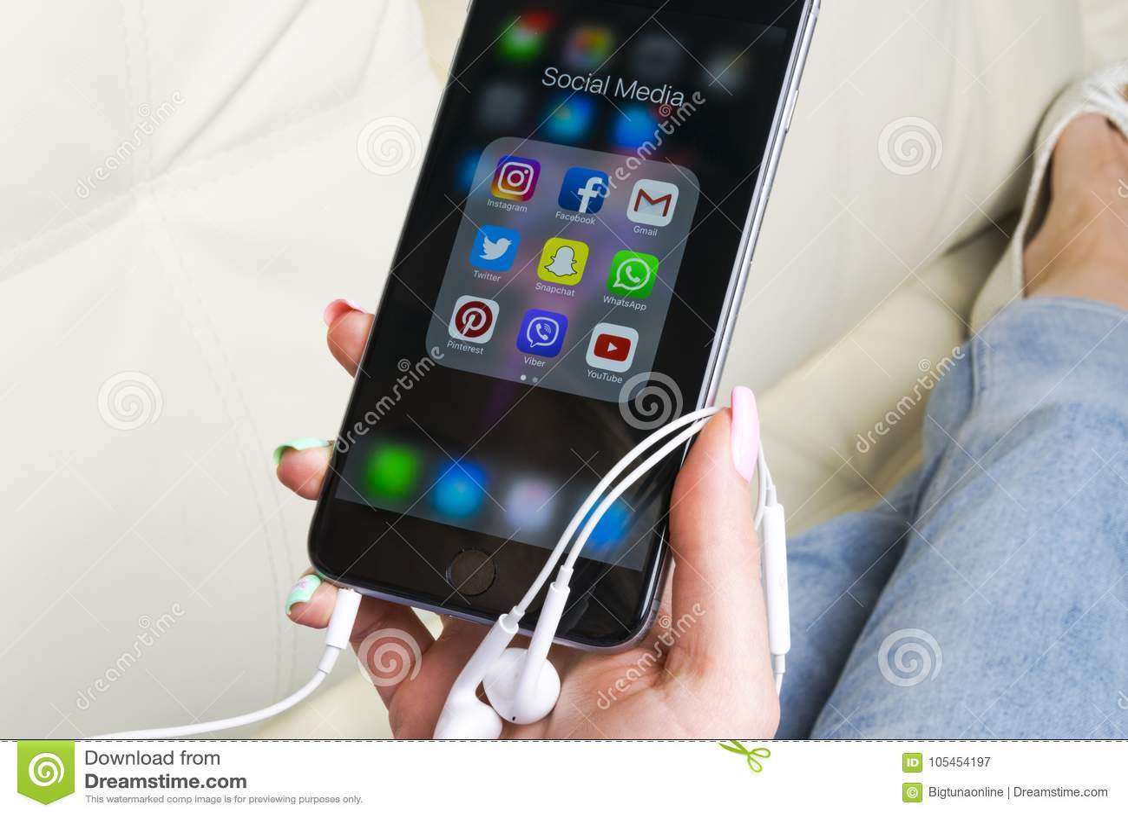 Manos de la mujer usando el iphone 7 con los iconos del medios facebook social, instagram, gorjeo, uso de Google en la pantalla C