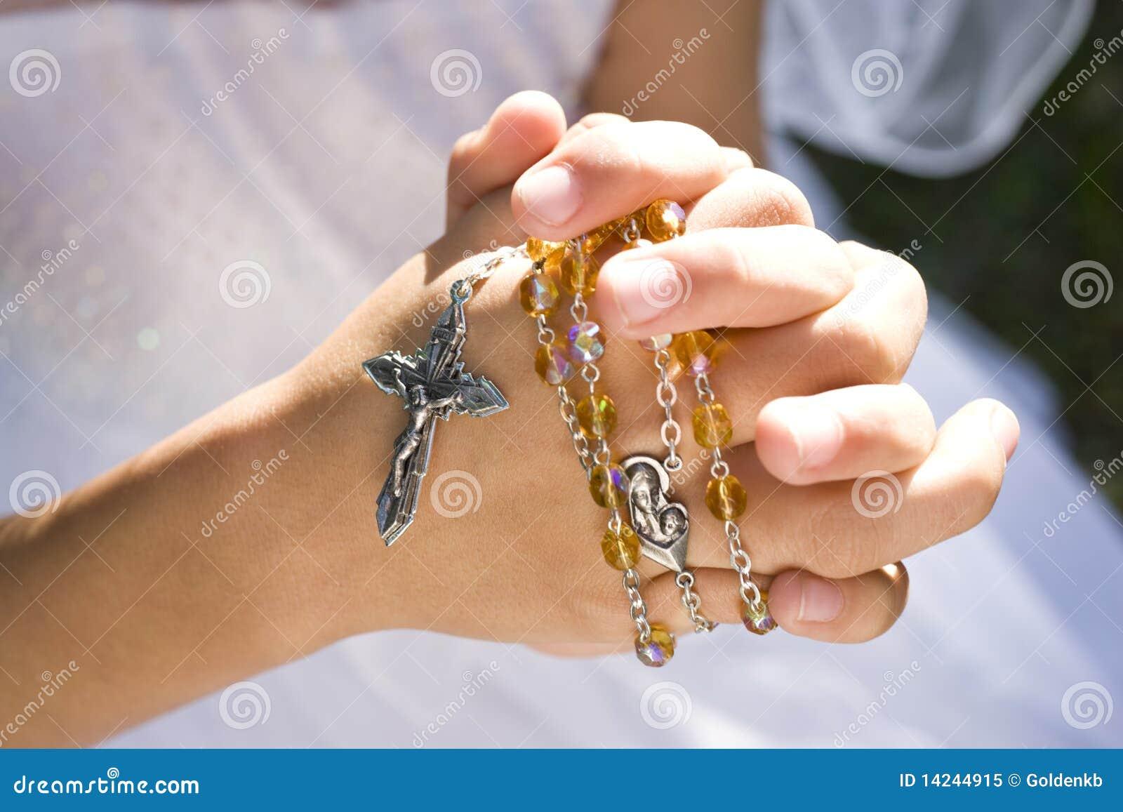 Manos de los granos y de la cruz del rosario de la explotación agrícola del niño