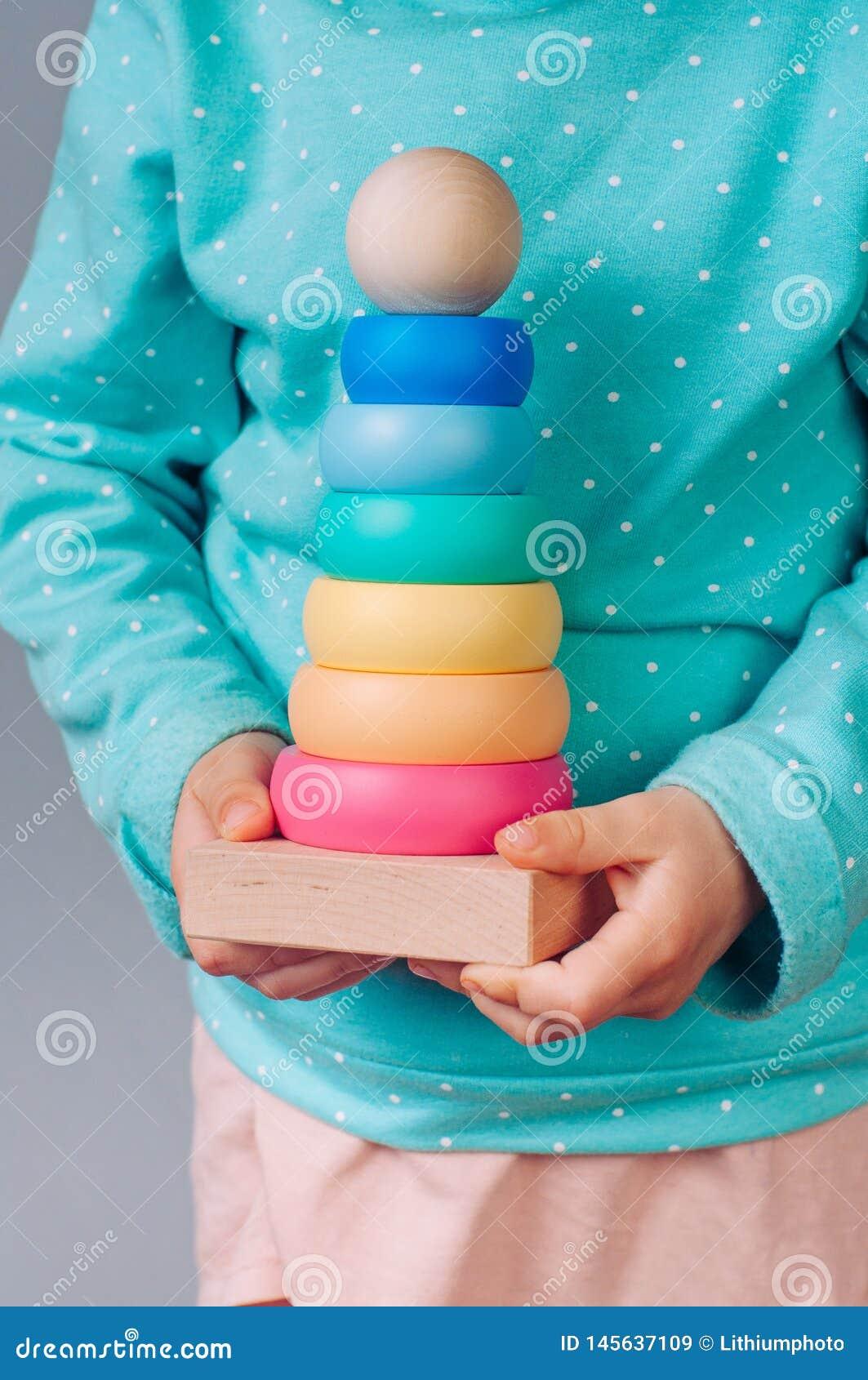 Manos de los niños que sostienen un juguete de la pirámide