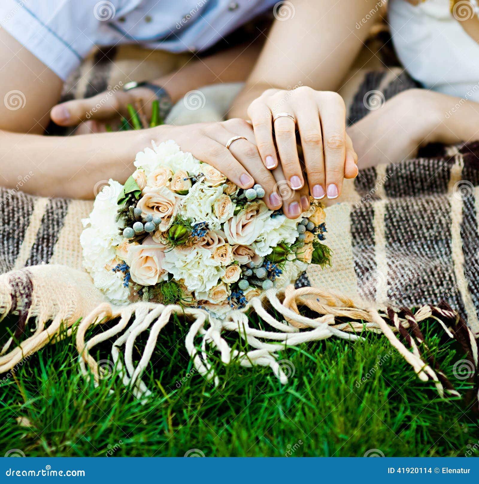 Manos de novia y del novio con los anillos de bodas (foco suave)
