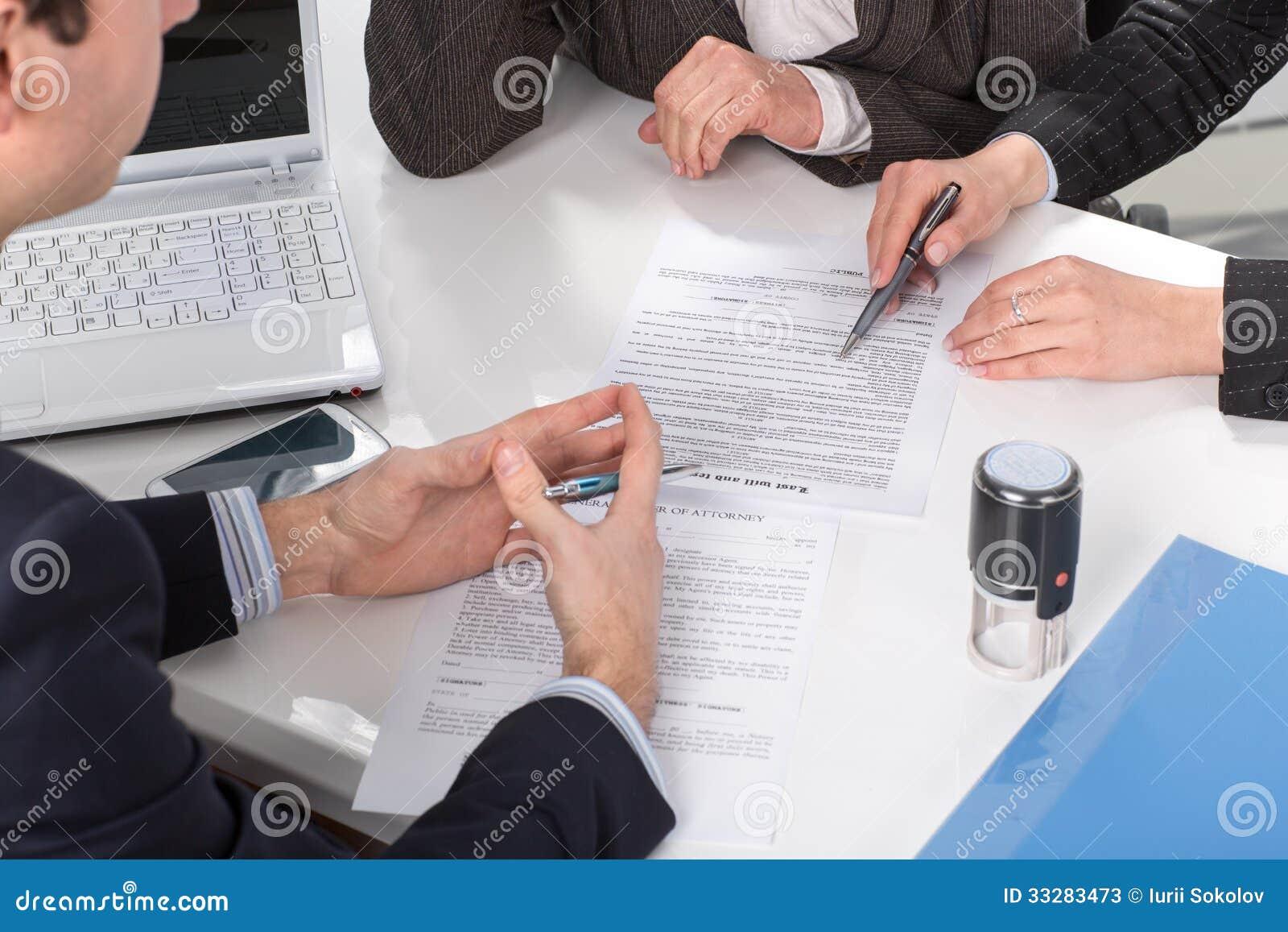 Manos de tres personas, documentos de firma