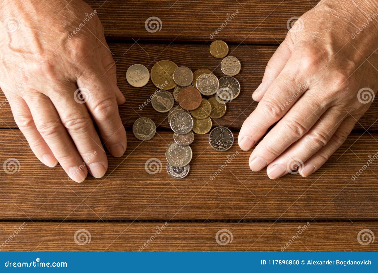 Manos de un hombre mayor con las diversas monedas en una tabla de madera Th