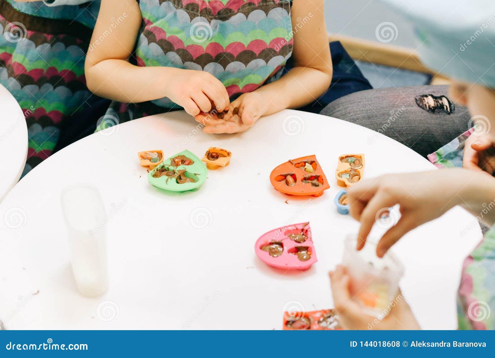 Manos de un niño, de una clase principal en cocinar el chocolate, de la fruta plegable y del chocolate en moldes