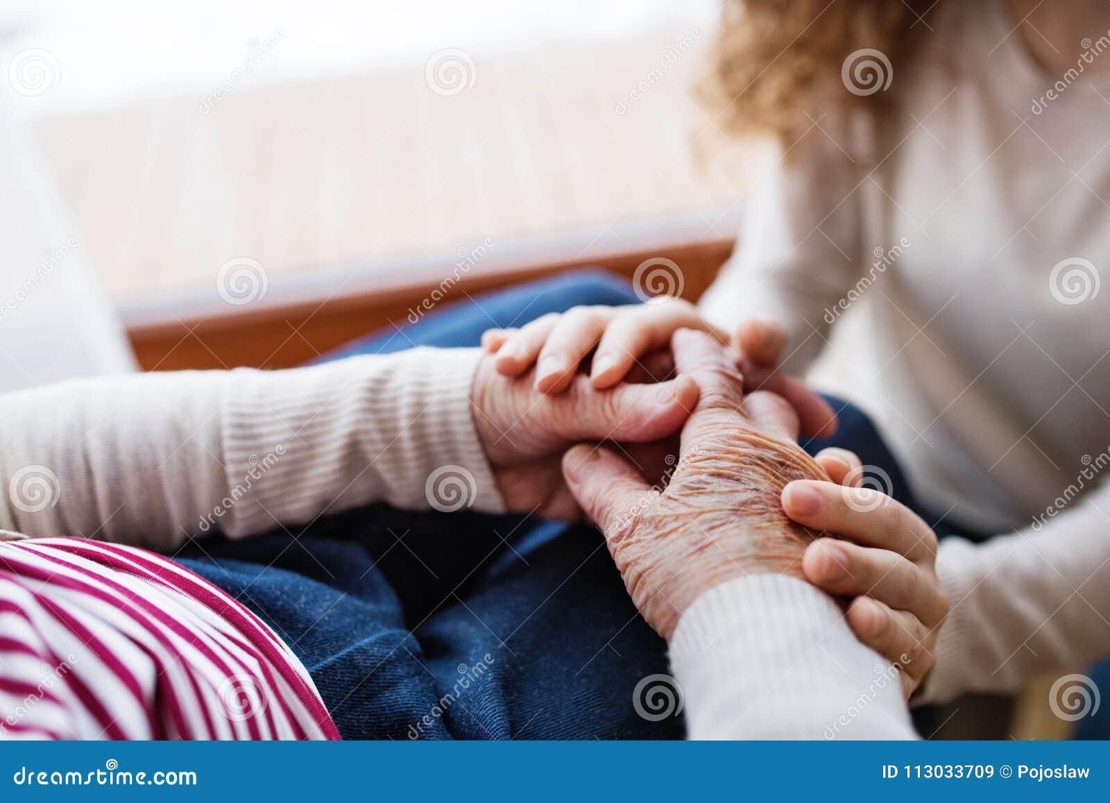 Manos del adolescente y de su abuela en casa
