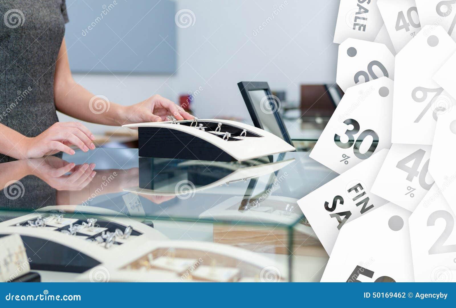 Manos del ayudante de la compensación en la caja de ventana con los anillos de diamante