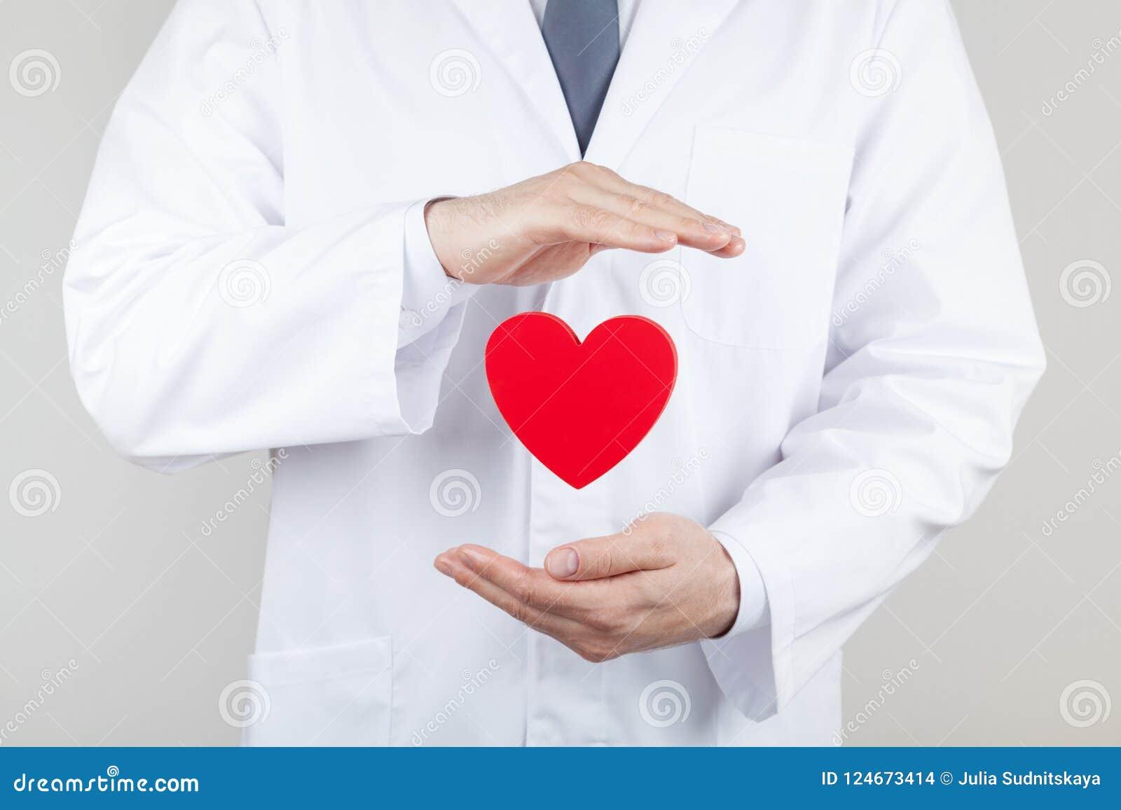 Manos del cardiólogo del doctor con el corazón del vuelo Cardiología y concepto de la enfermedad cardíaca