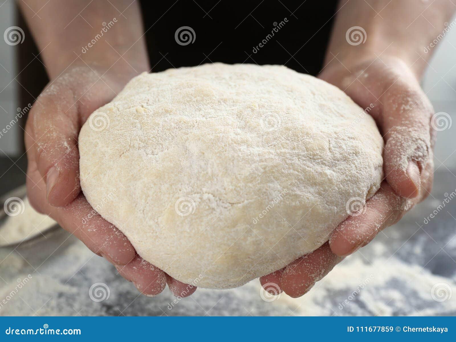 Manos del cocinero con pasta en cocina