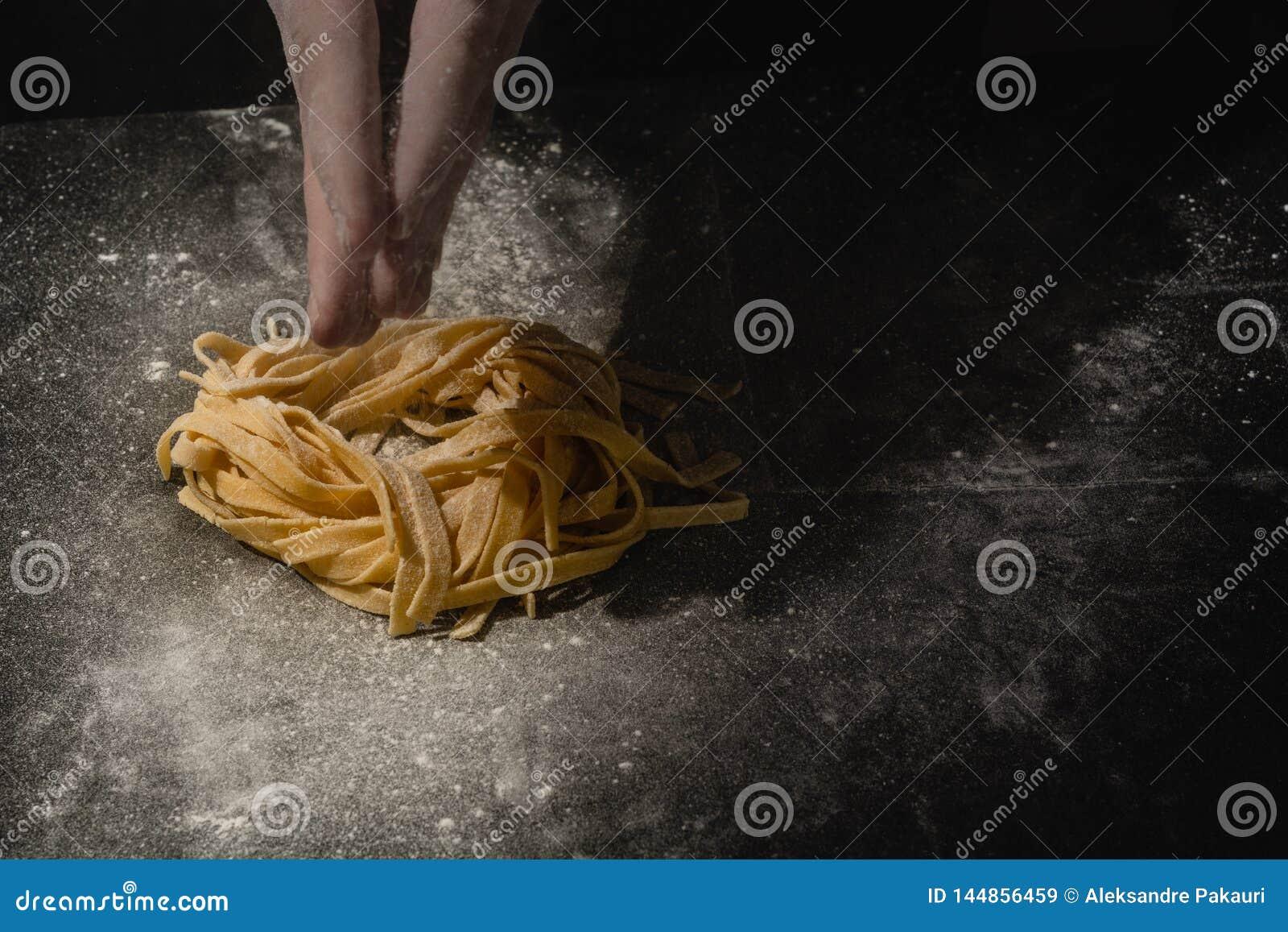 Manos del cocinero que hacen los espaguetis, pastas, tallarines con las pastas frescas en la tabla negra con