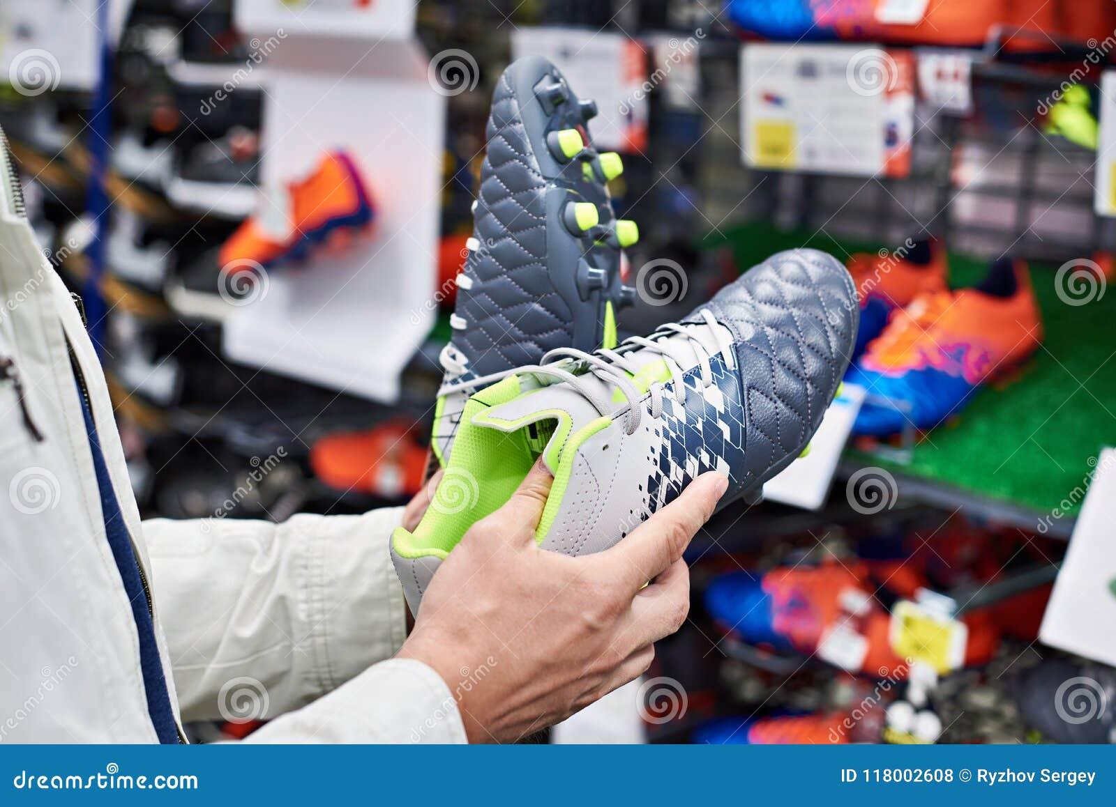 9b98f438a694e Manos de un hombre con las botas del fútbol en una tienda de los deportes