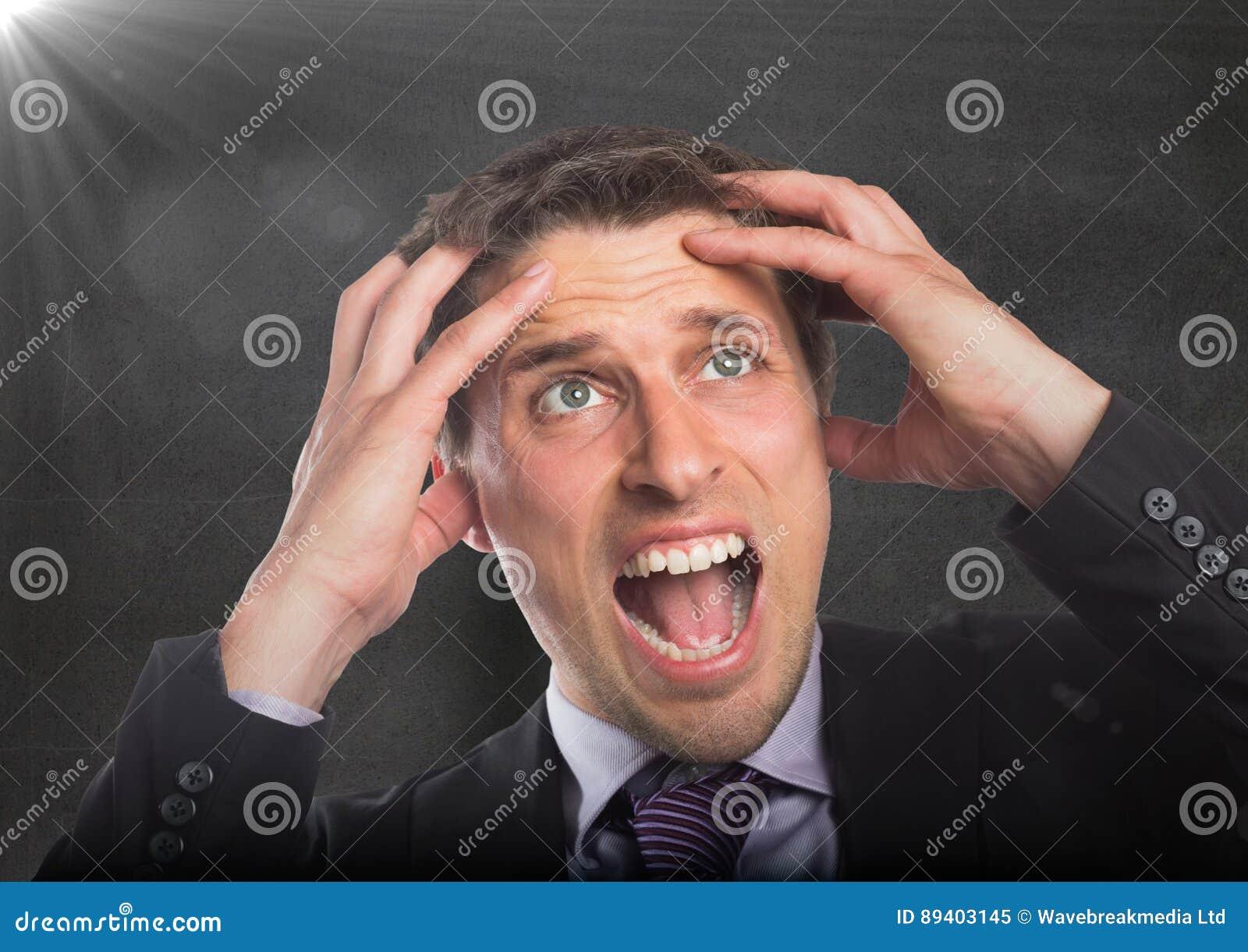 Manos del hombre de negocios en la cabeza contra el muro de cemento con la llamarada