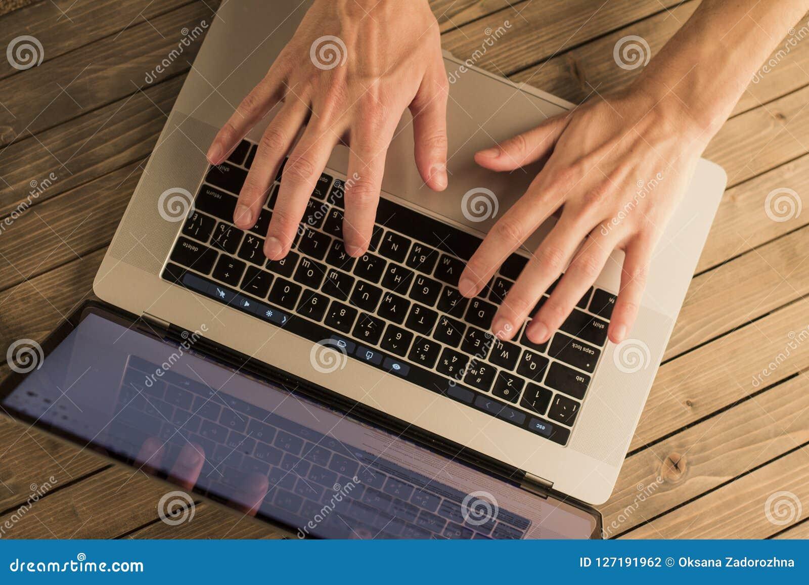 Manos del hombre en el teclado del ordenador portátil Visión superior