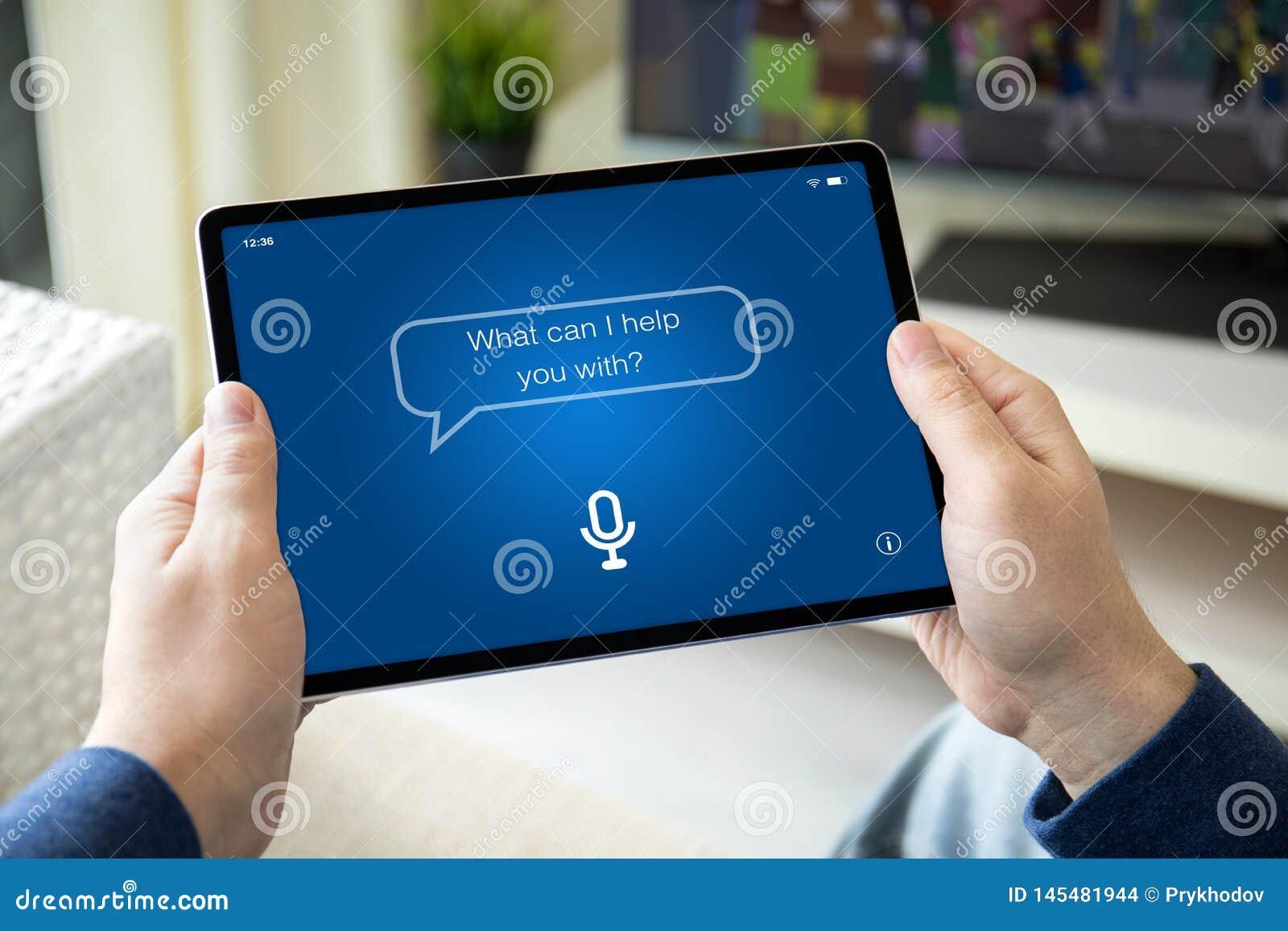 Manos del hombre que sostienen la tableta del ordenador con el ayudante personal del app