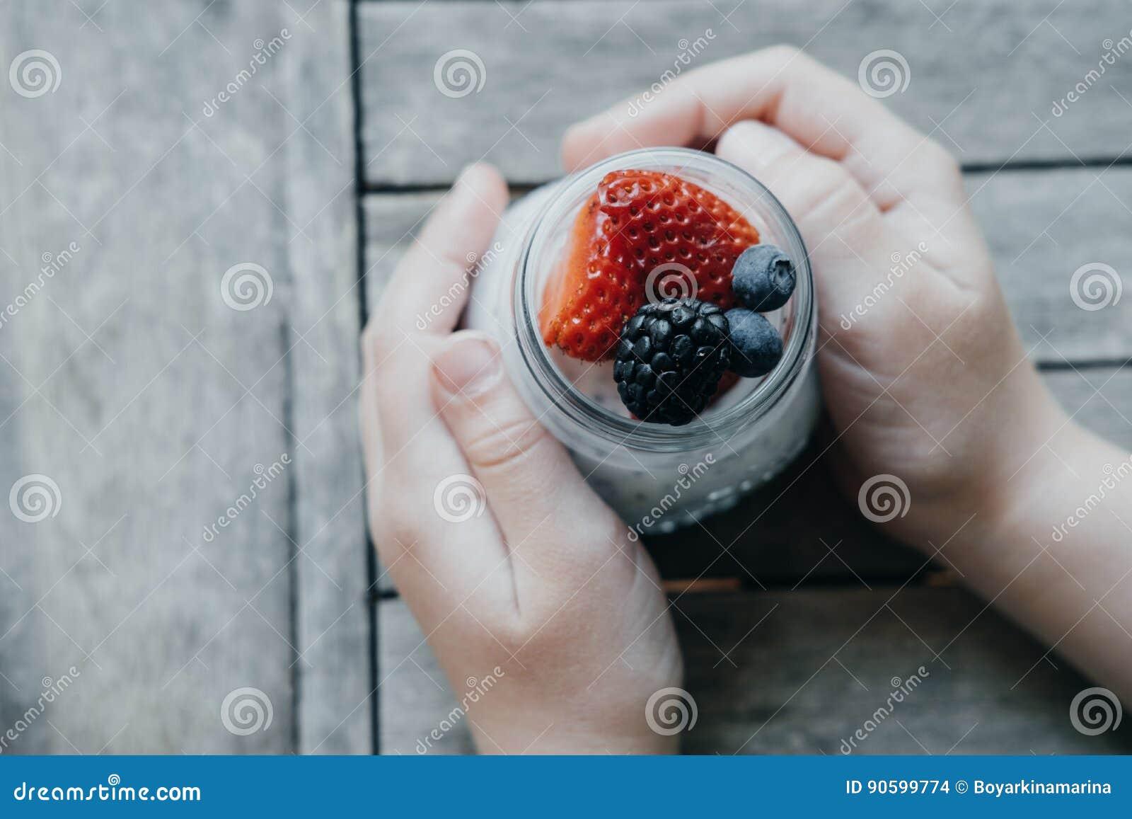 Manos del muchacho con el pudín con las semillas del chia, el yogur y las frutas frescas: