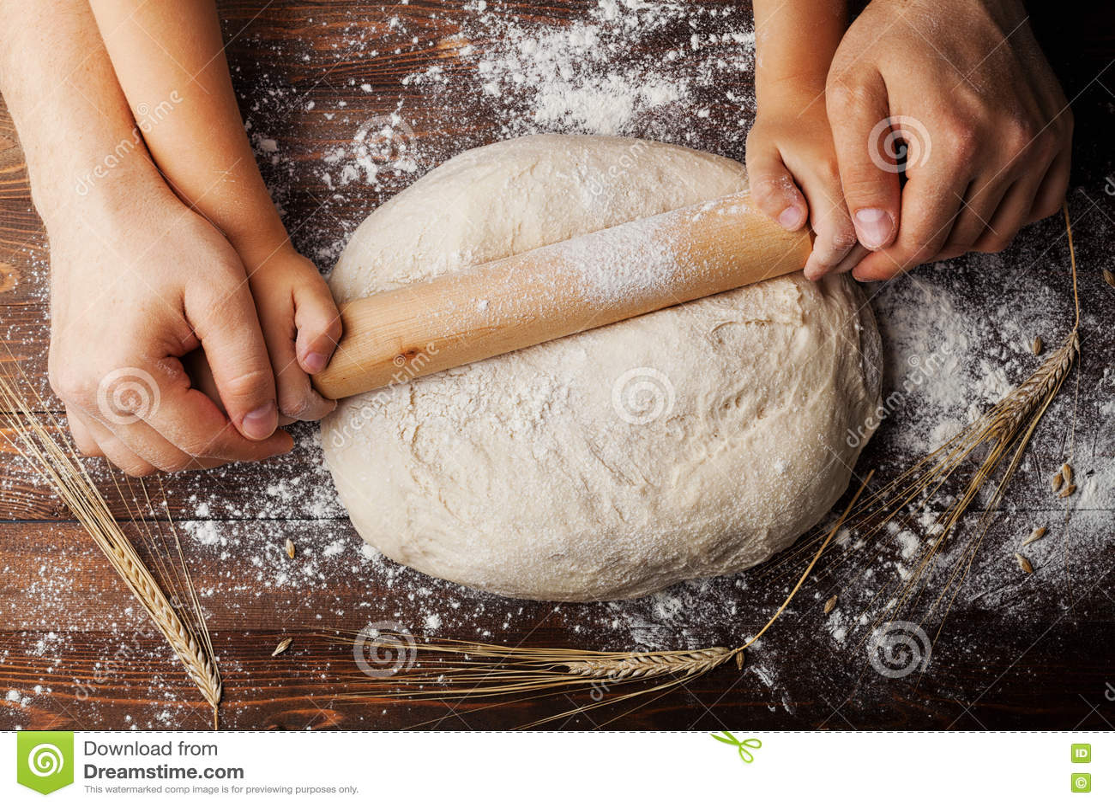 Manos del padre y del niño que hacen la pasta con los oídos de la harina, del rodillo y del trigo en la opinión de sobremesa de m
