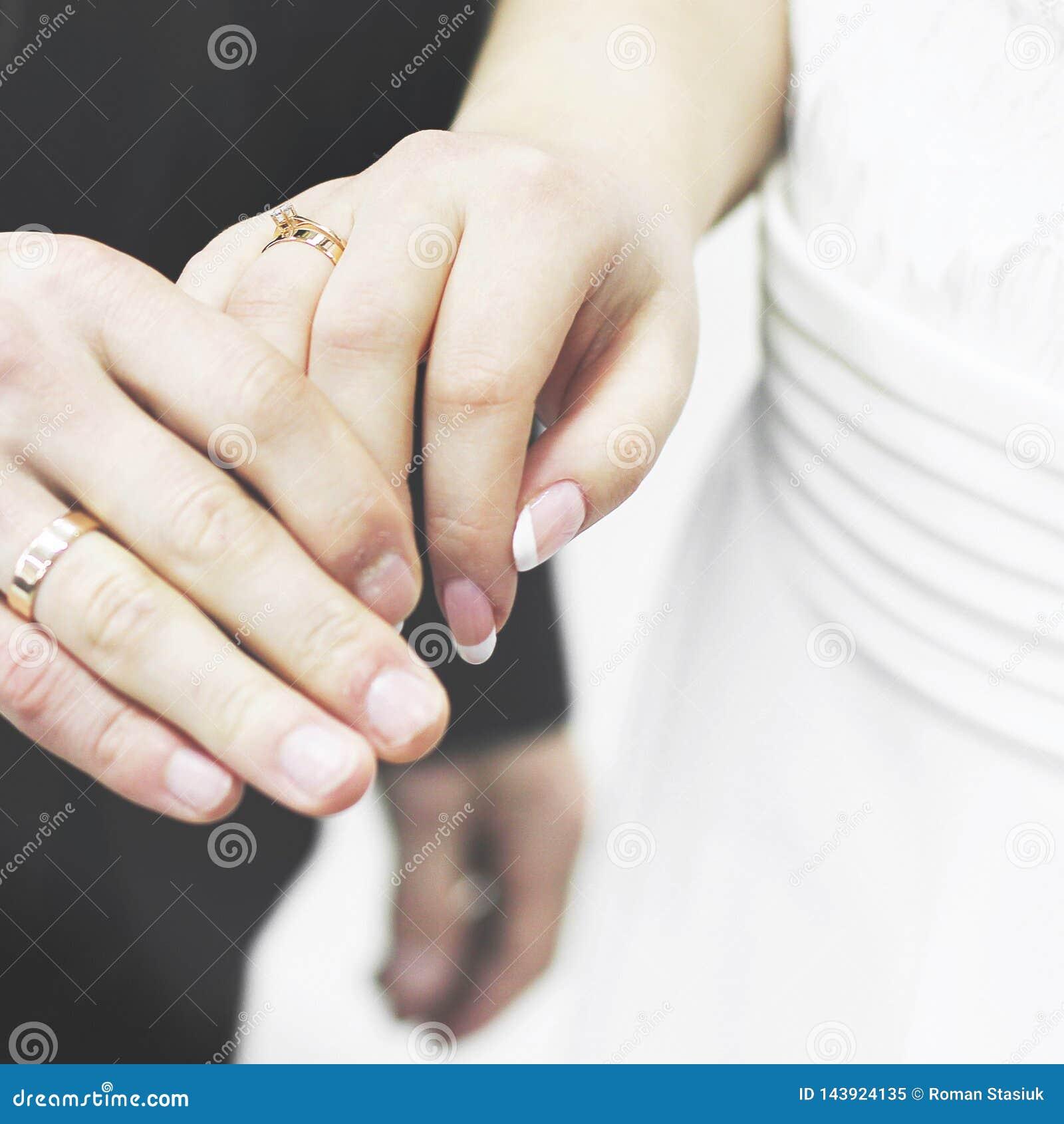 Manos del primer de novia y del novio