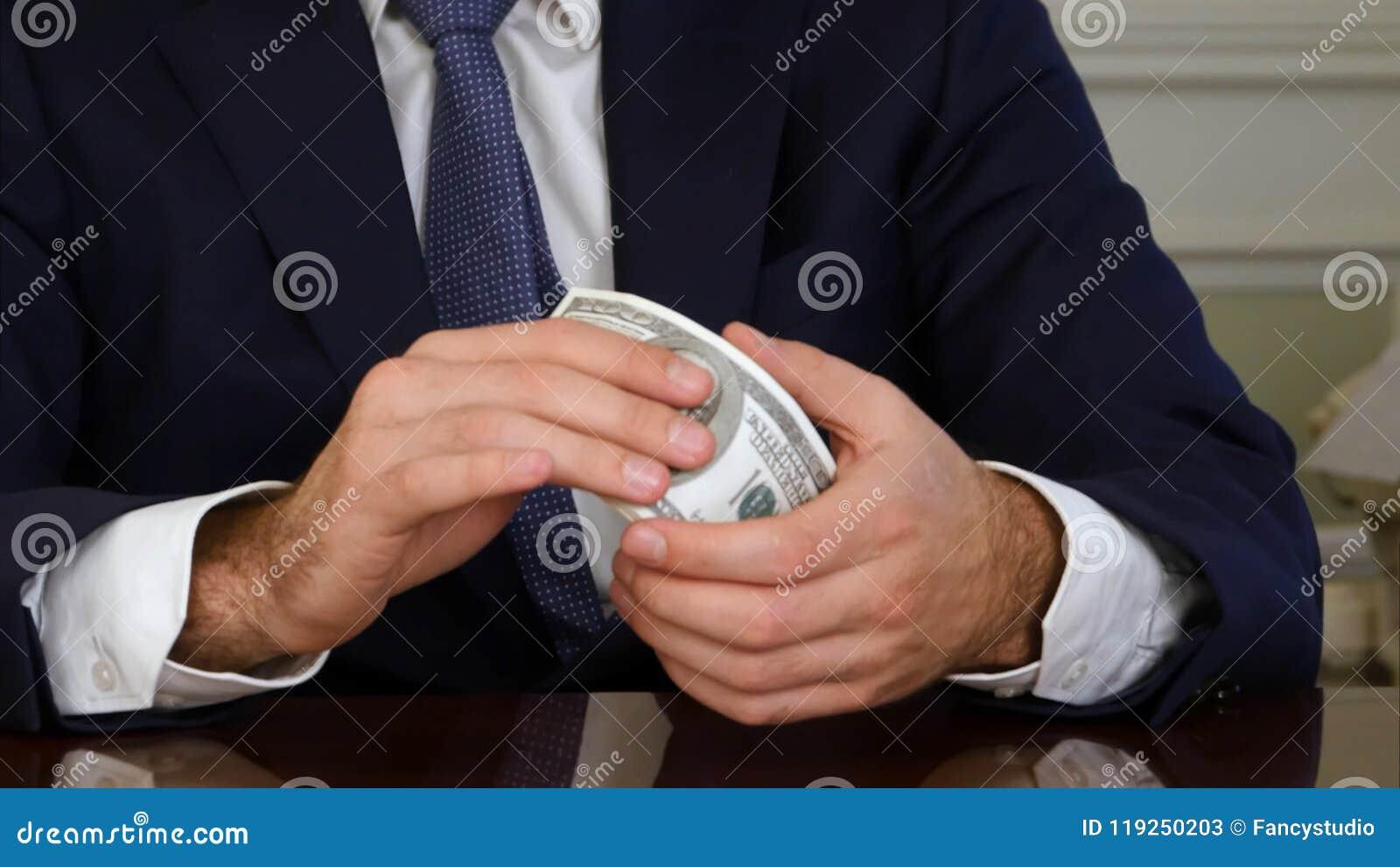 Manos del ` s del hombre que llevan a cabo billetes de dólar del dinero