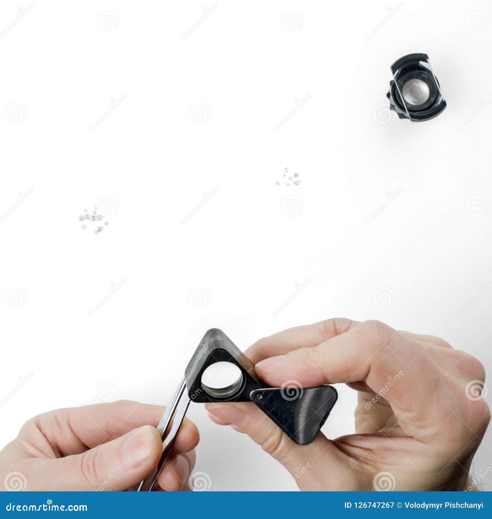 Manos del tasador con una lupa y las pinzas Evaluación del diamante